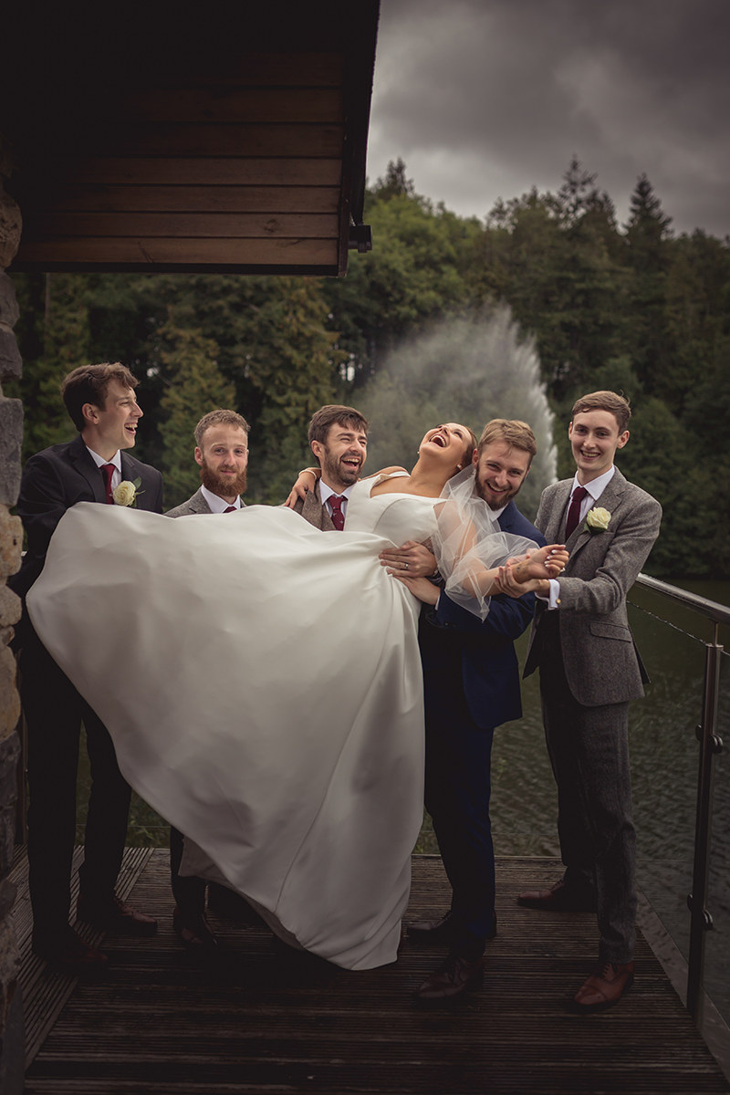 laughing bride being held by the groom at the groomsmen at Canada Lodge and Lake