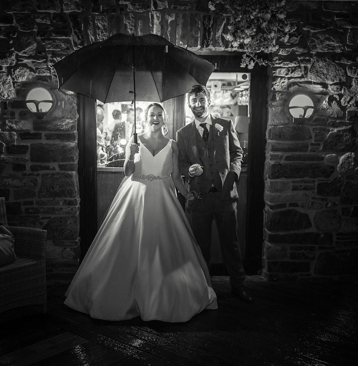 Bride and groom in the rain under an umbrella smoking a cigar