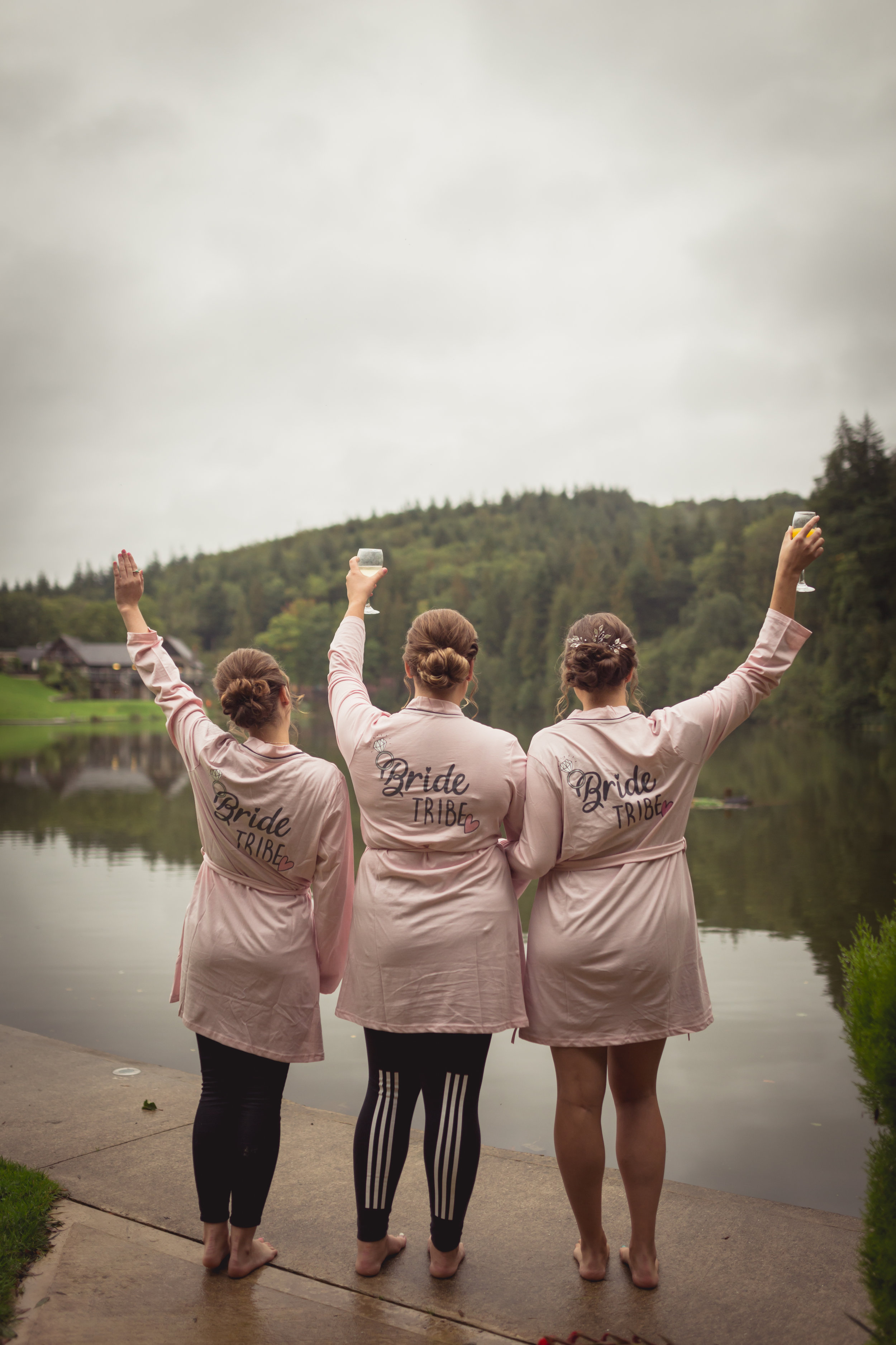 Bridemaids raising a glass of champagne ovelooking the lake at Canada Lodge a south wales wedding venue