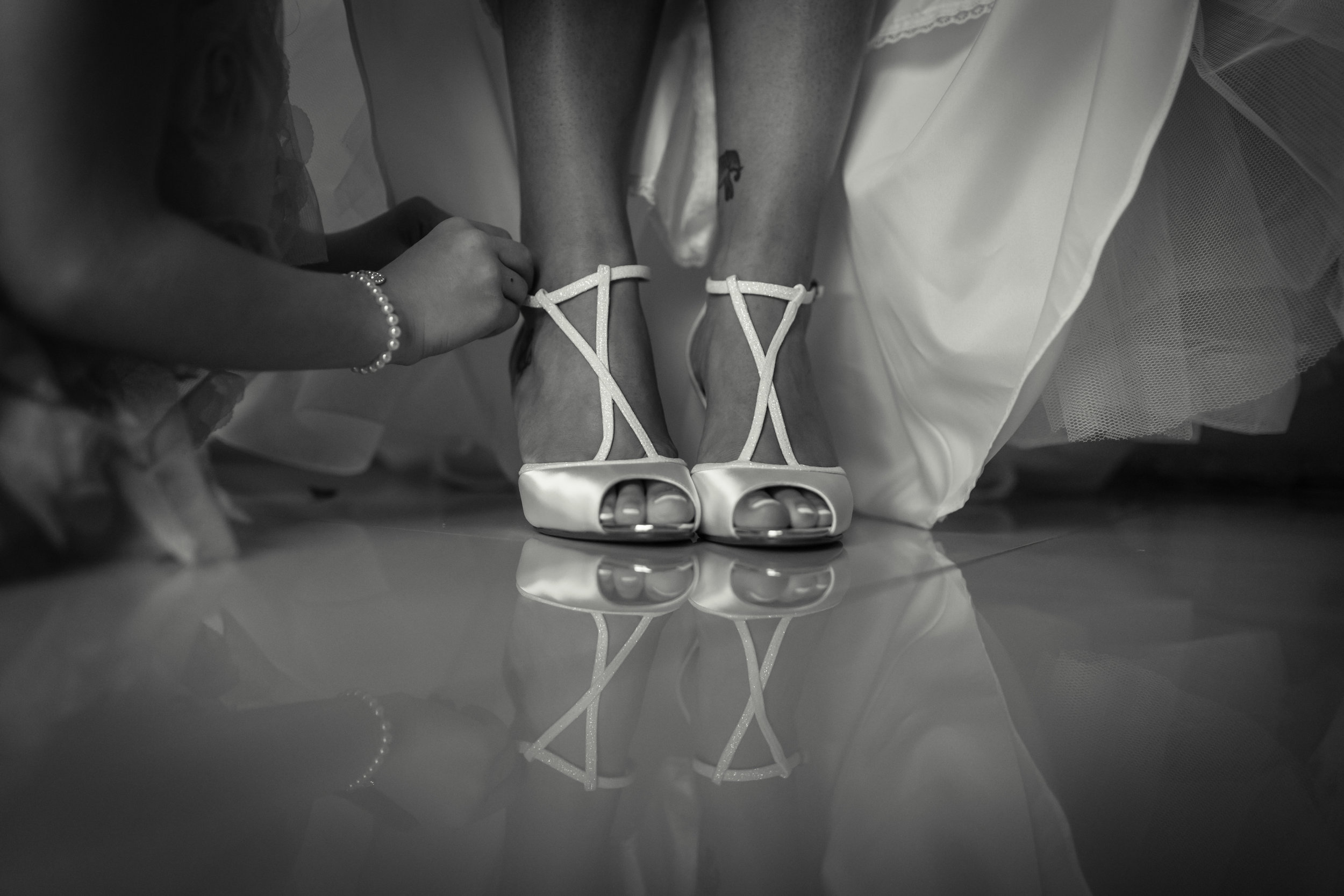 Black and white close up photograph of brides wedding shoes