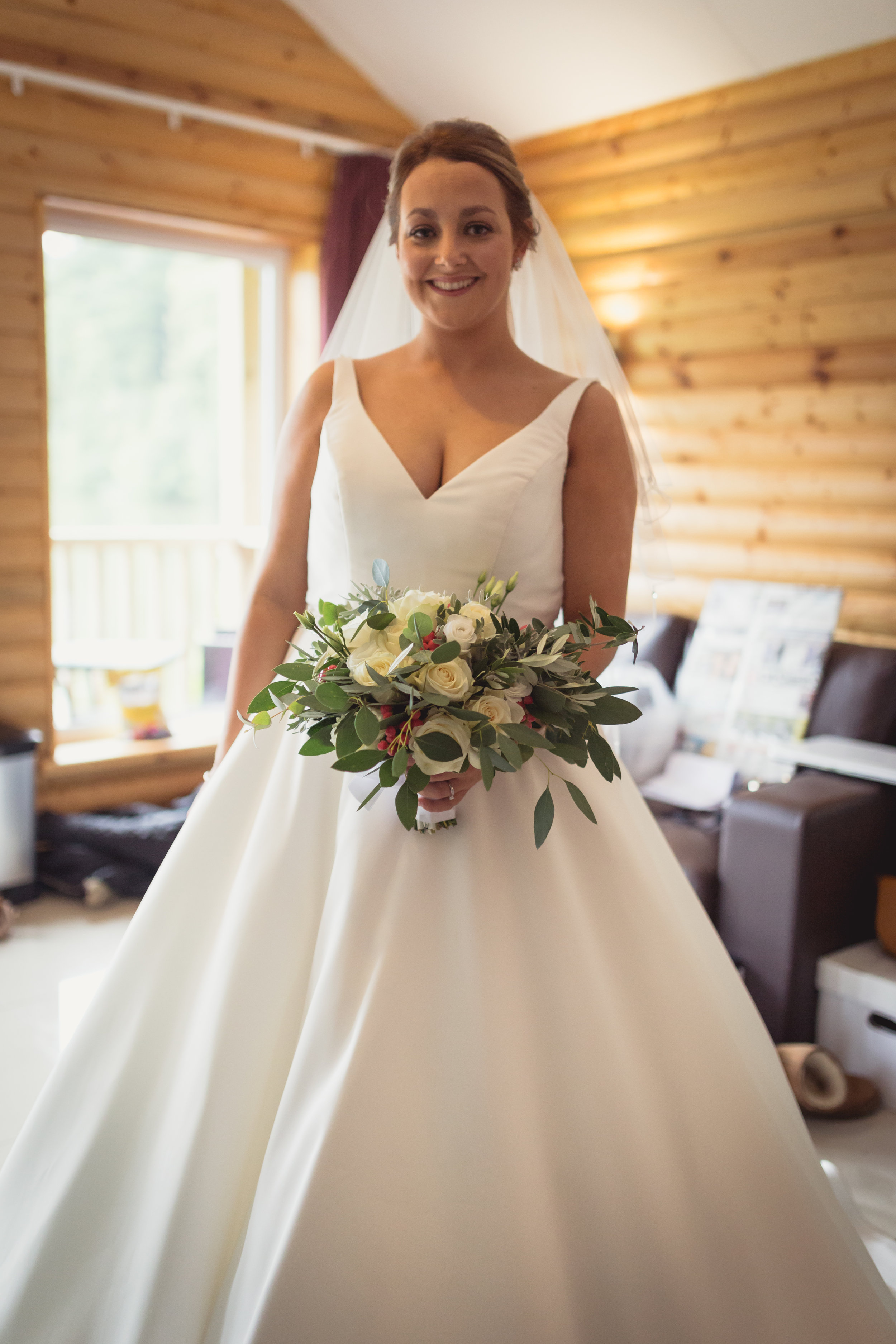 Bride holding her wedding flowers preparing to leave for the ceremony at a wedding in South Wales