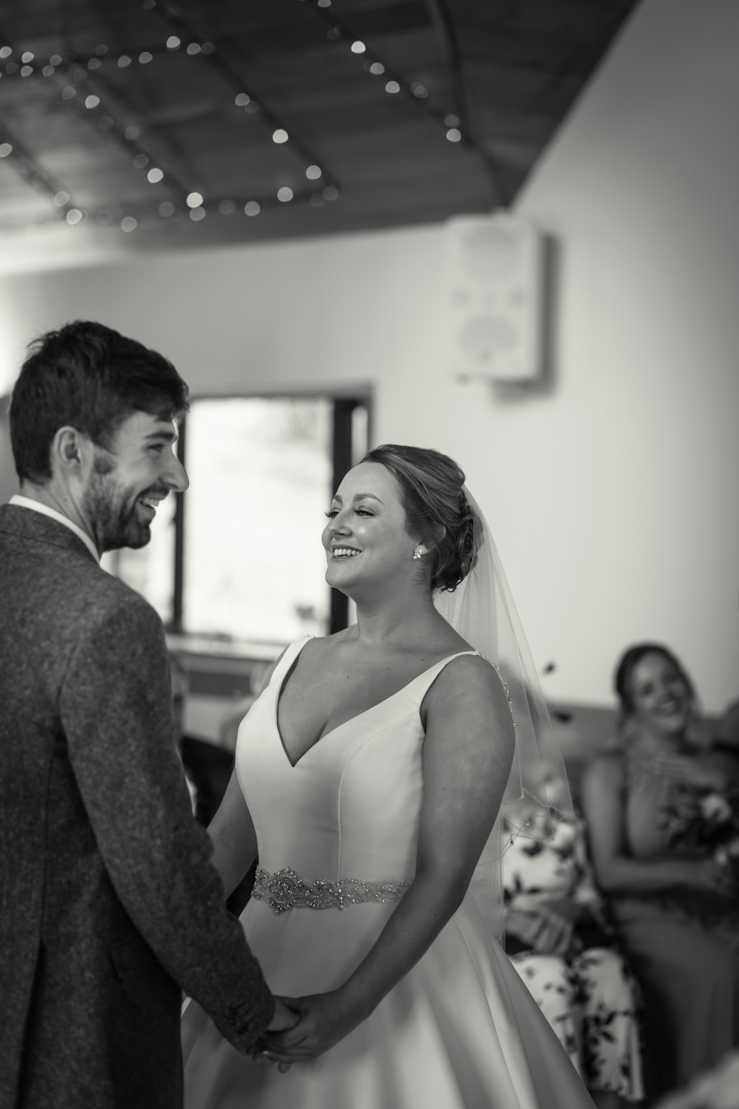 Black and white photograph of Bride and groom holding hands and looking at each other during their wedding ceremony