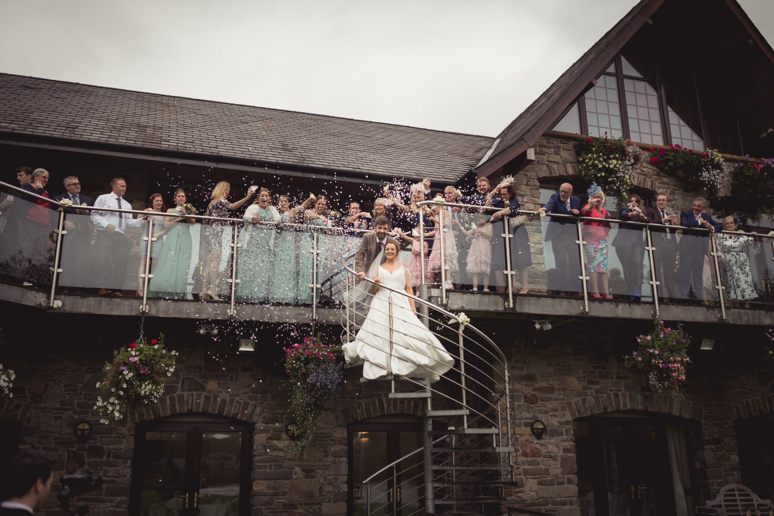 Bride and groom walking down a spiral staircase whilst the wedding guests throw confetti over them from above
