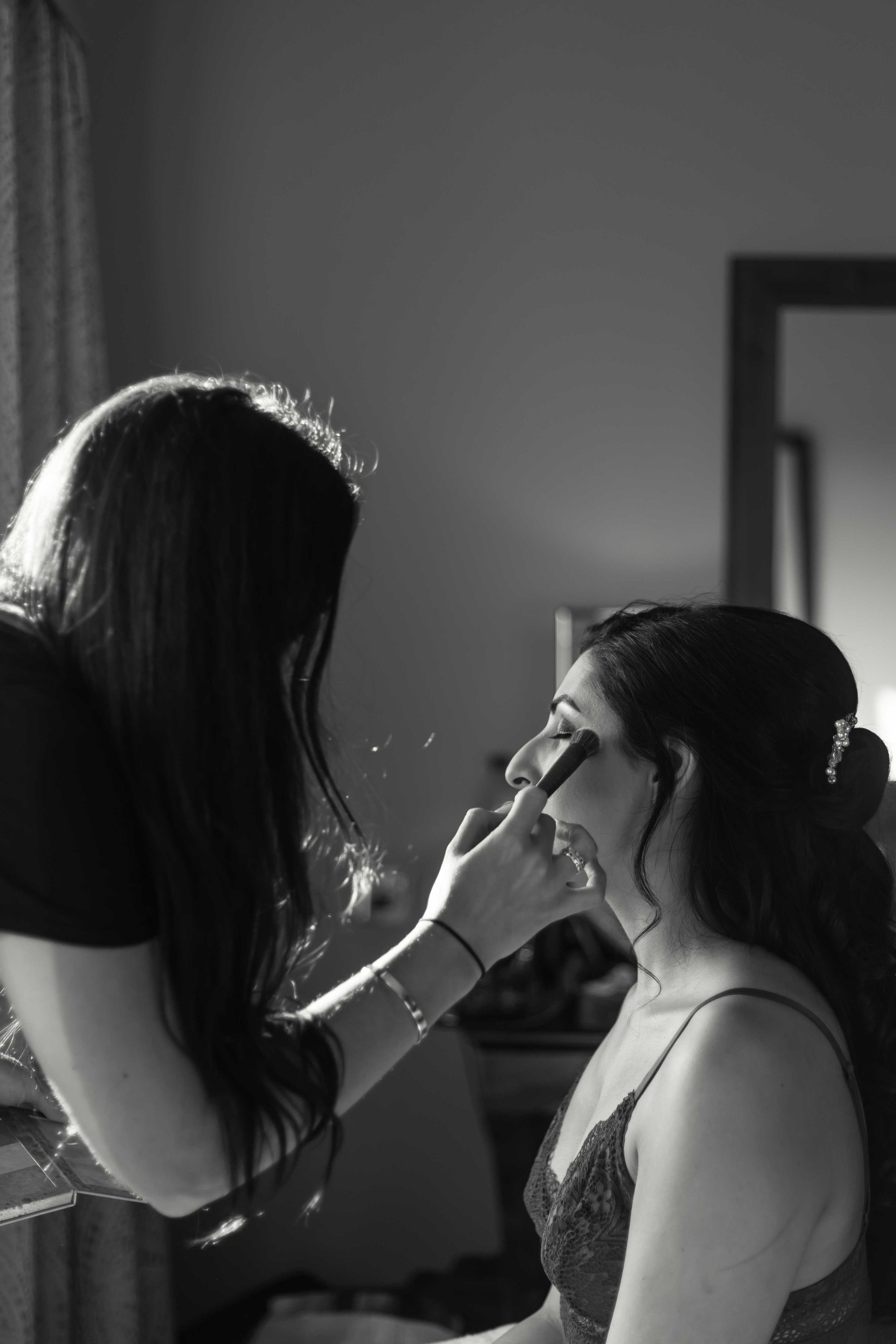 Black and white photograph of bride having make up applied at Celtic Manor Resort