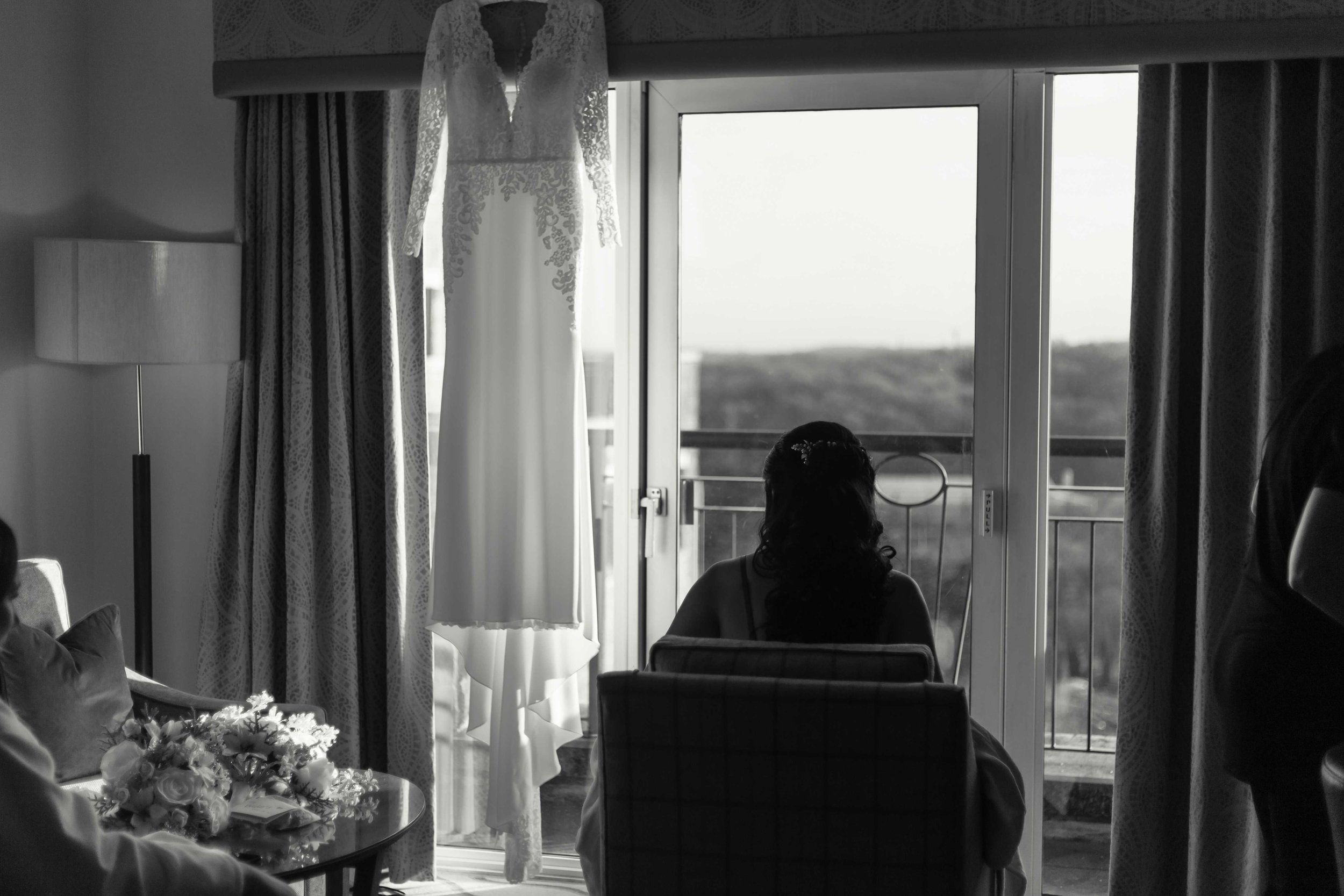 Black and white photograph of bride sitting and looking out of window