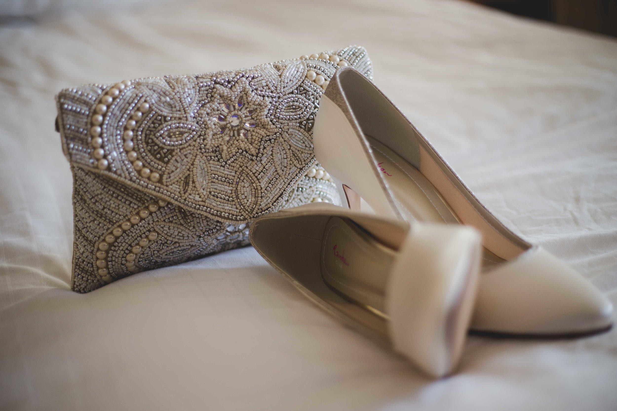 Close up photograph of brides shoes and handbag