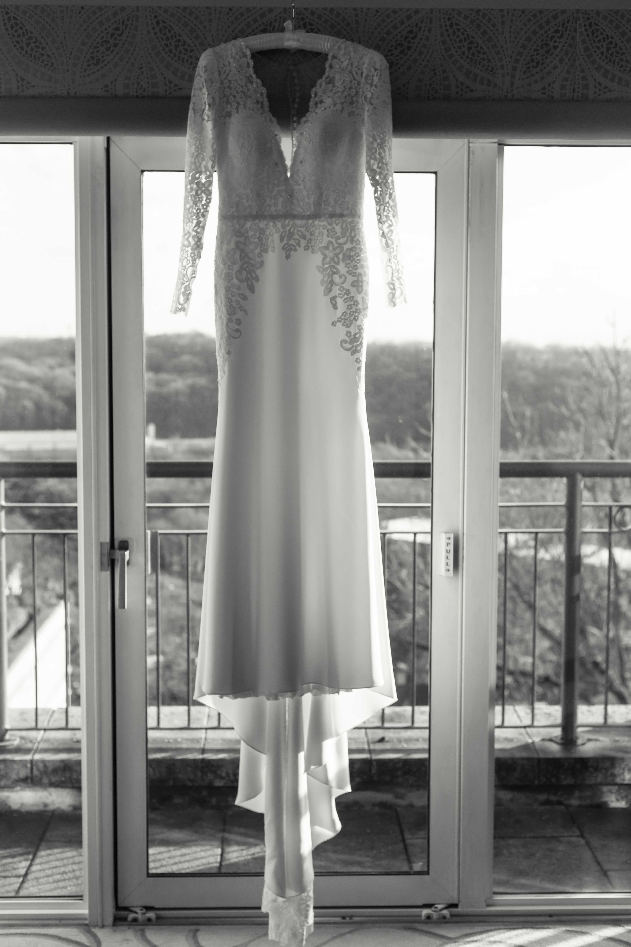 Black and white photograph of brides wedding dress hanging in large window