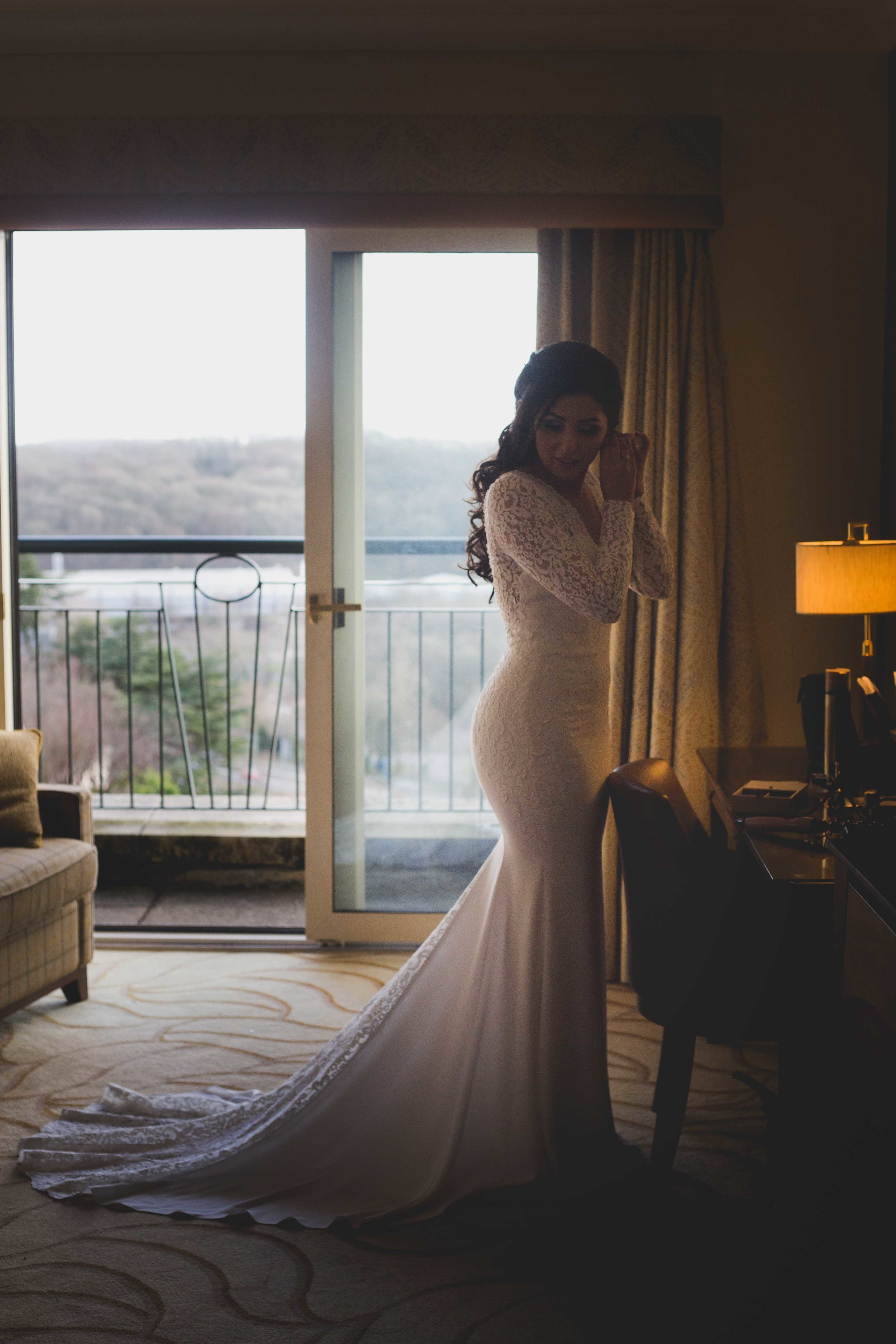 Portrait image of bride getting ready and putting on earrings