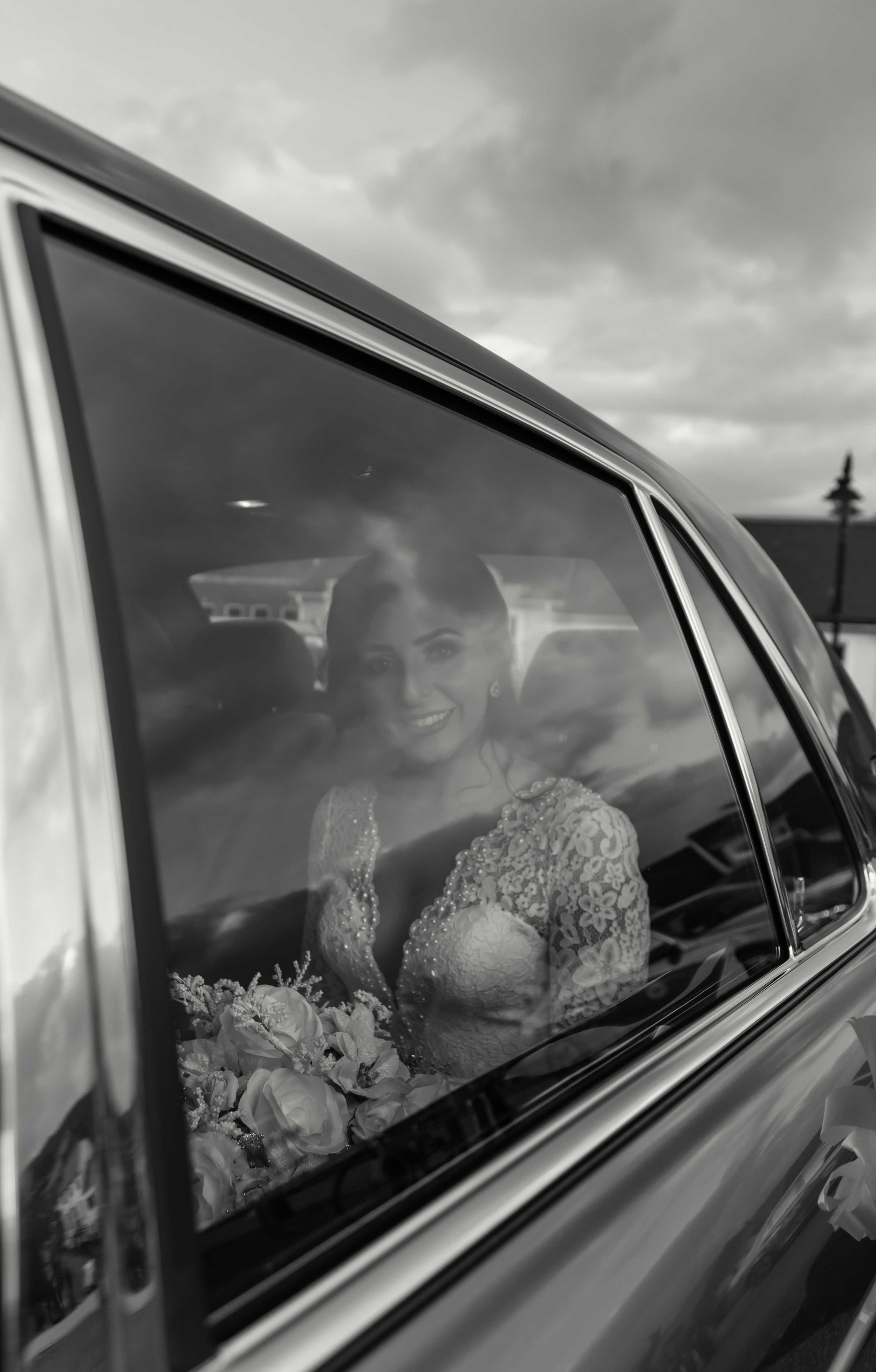 Black and white photograph of brid shot through the window of the wedding car