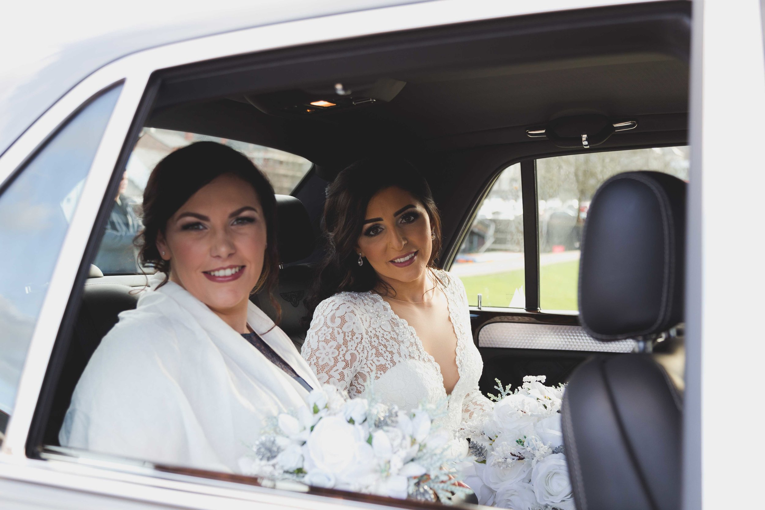 Bride and bridesmaid sat in back of wedding car just before the wedding ceremony