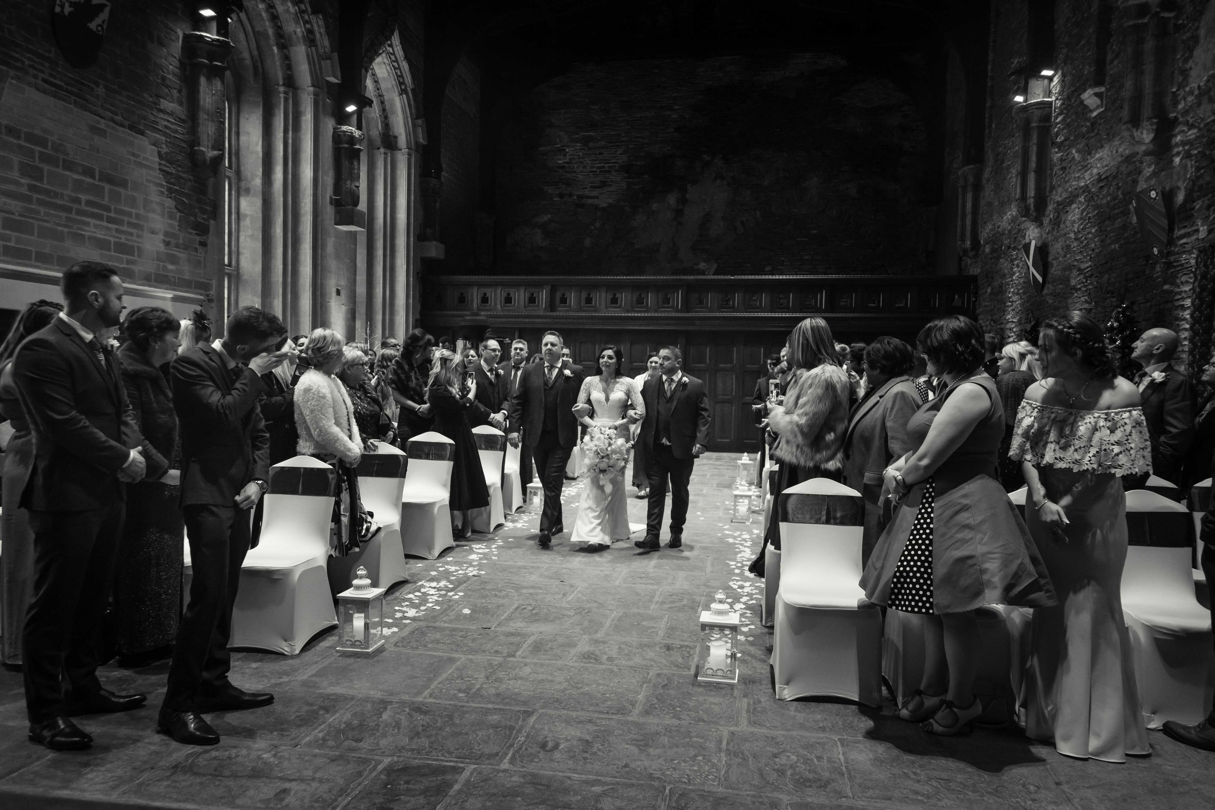 Black and white photograph of the bride walking up the aisle at wedding ceremony at Caerphilly Castle