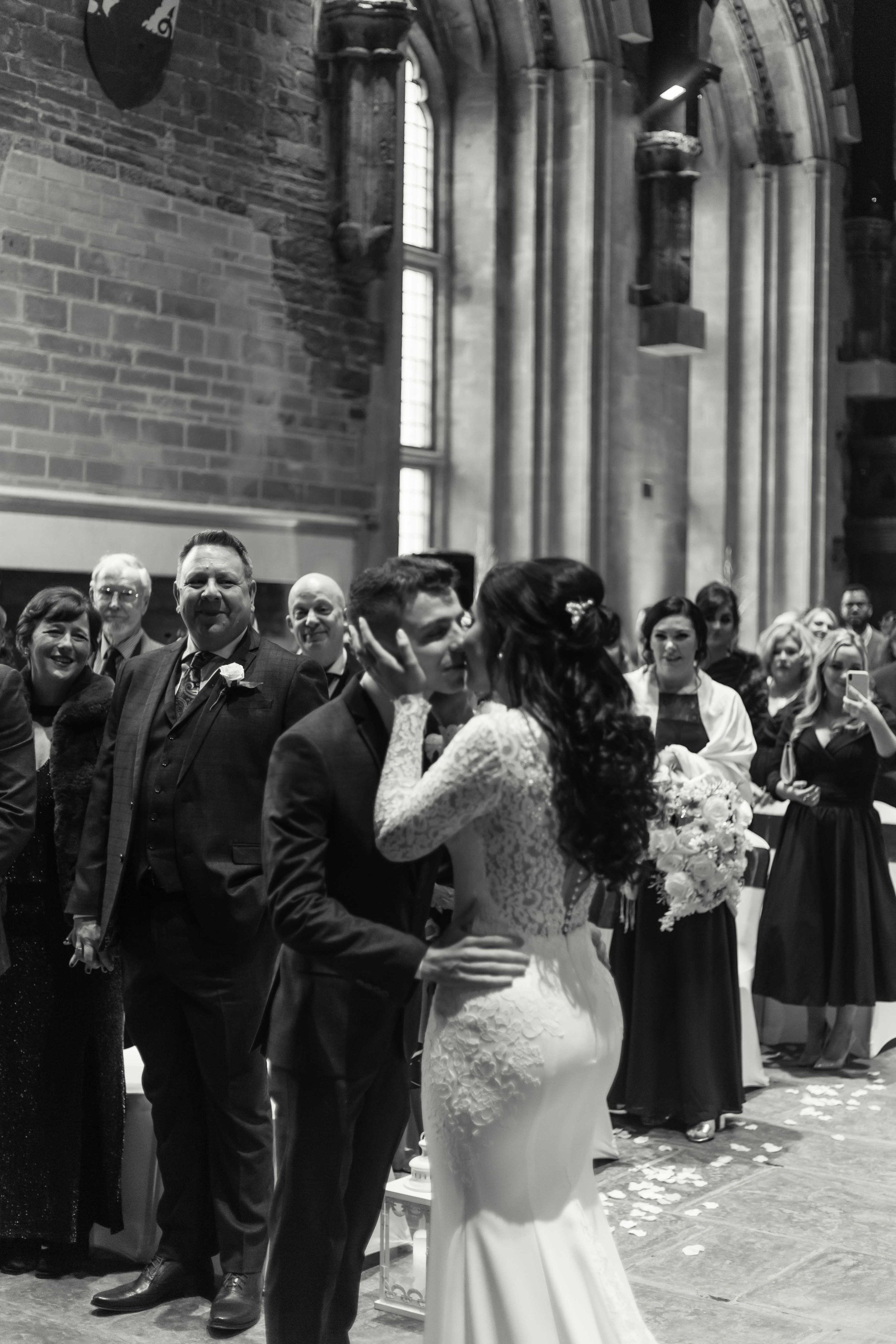 Black and white image of bride and groom enjoying their first kiss