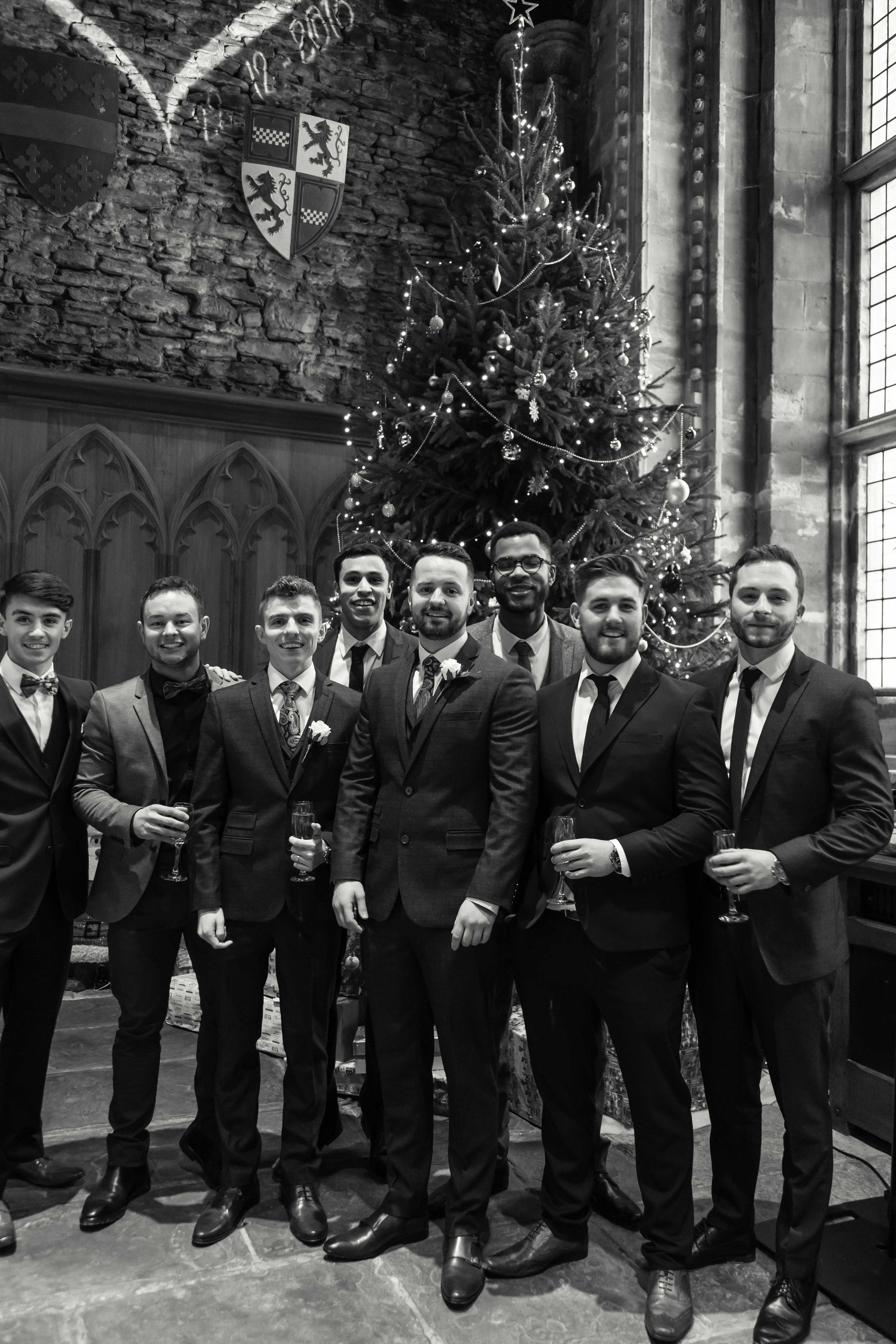 Black and white image of groom with friends next to a large christmas tree at Caerphilly Castle
