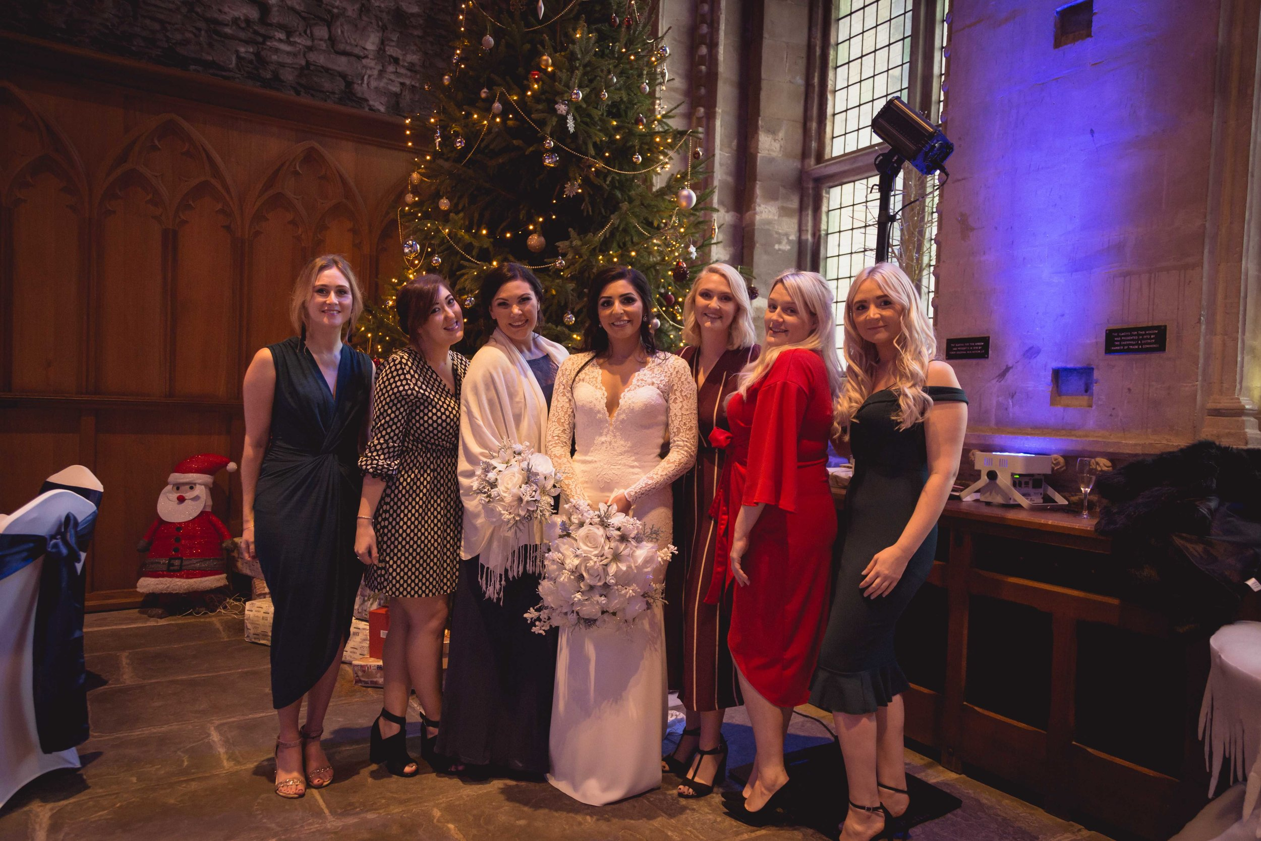 Image of bride with friends next to a large christmas tree at Caerphilly Castle