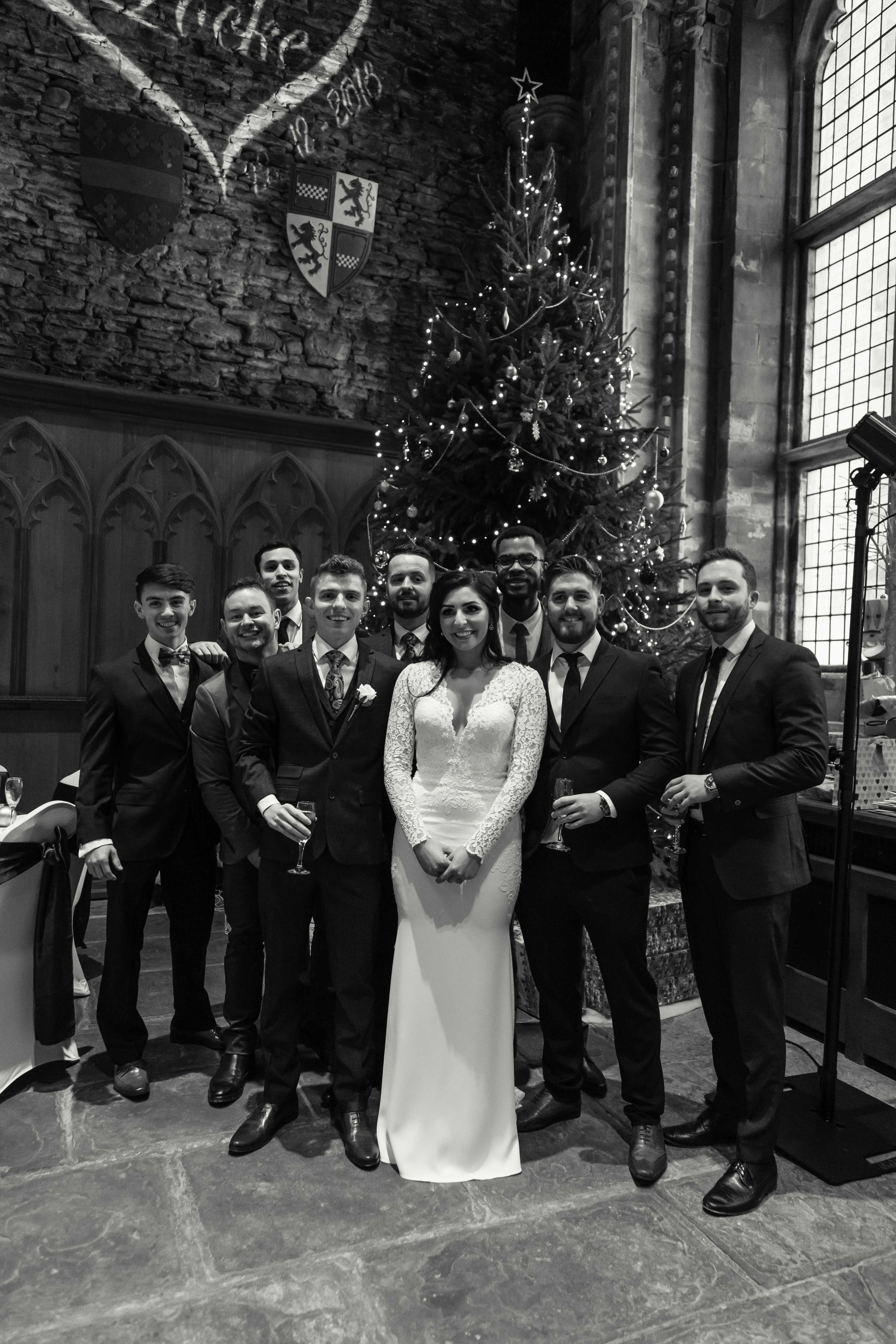 Black and white image of bride groom with friends next to a large christmas tree at Caerphilly Castle
