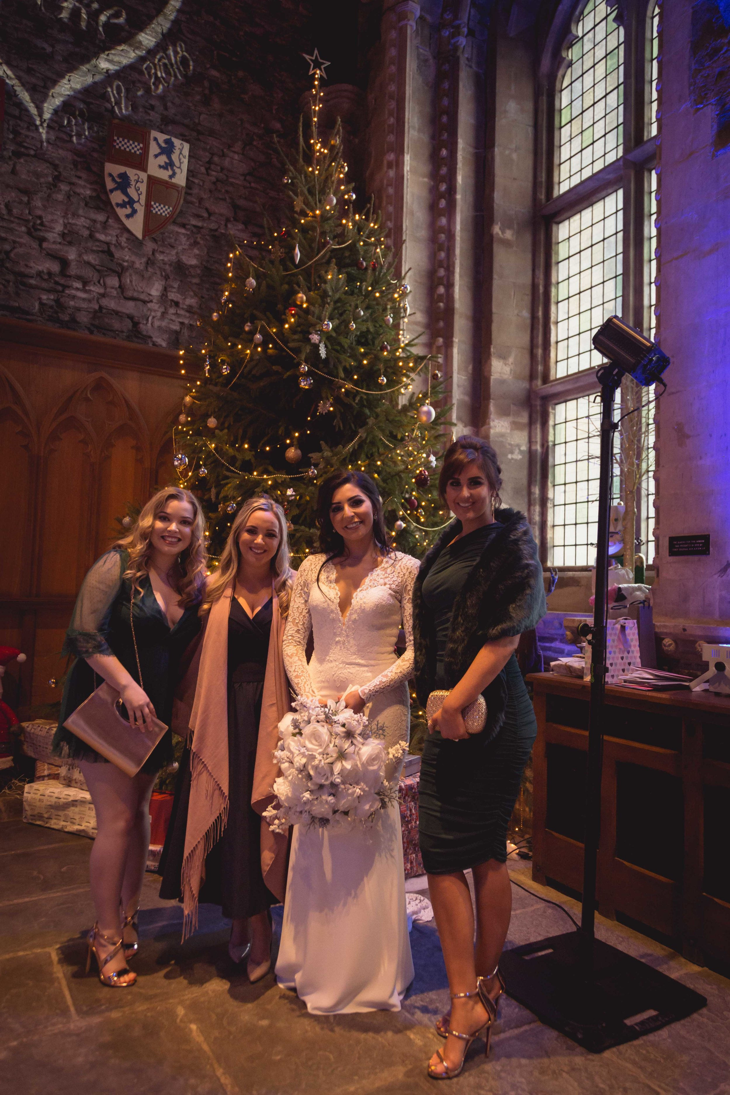 Image of bride with friends next to a large christmas tree at a South Wales Wedding