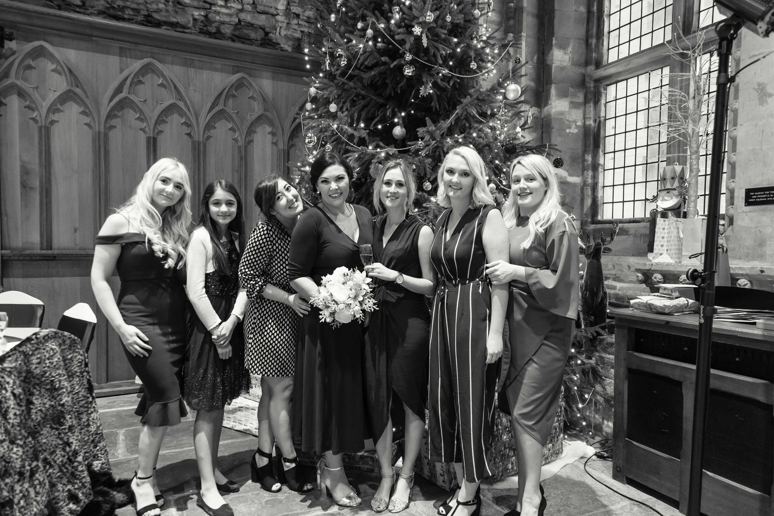 Black and white image of bride with friends next to a christmas tree at Caerphilly Castle