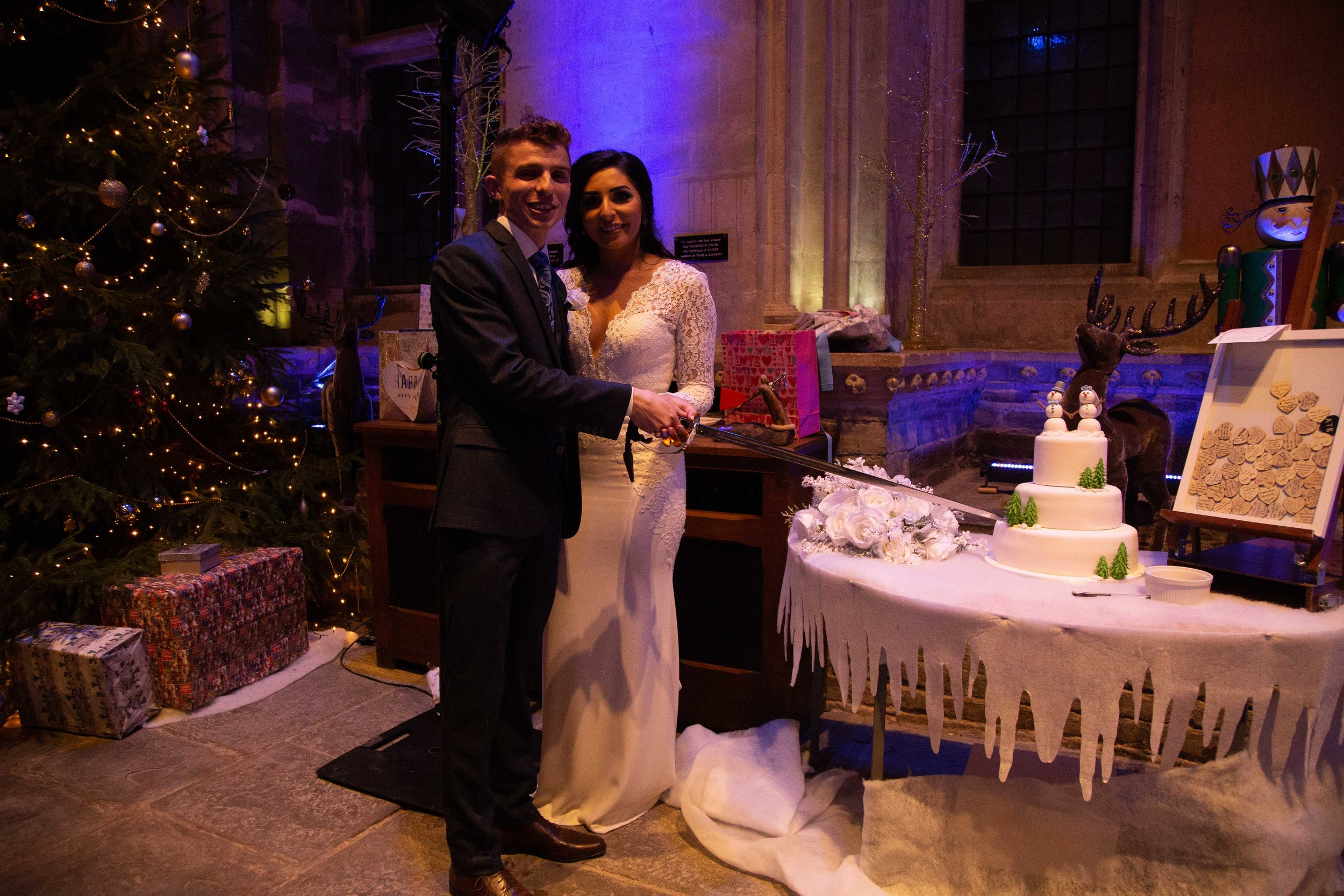 Bride and groom cutting the cake with a sword at Caerphilly Castle