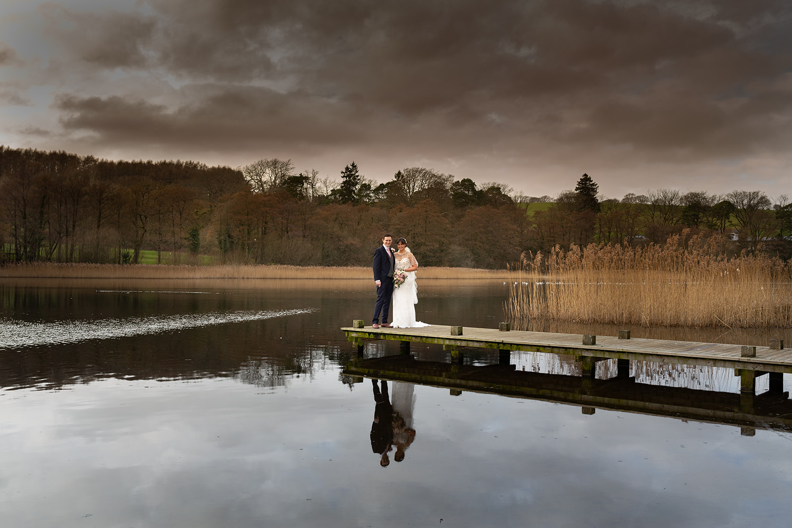 Bride and groom standing on a jetty in the lake at Hensol Castle, South Wales