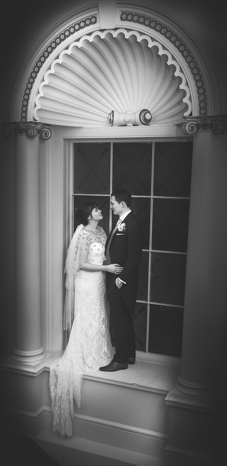 Black and white photograph of bride and groom on the stairs at Hensol Castle