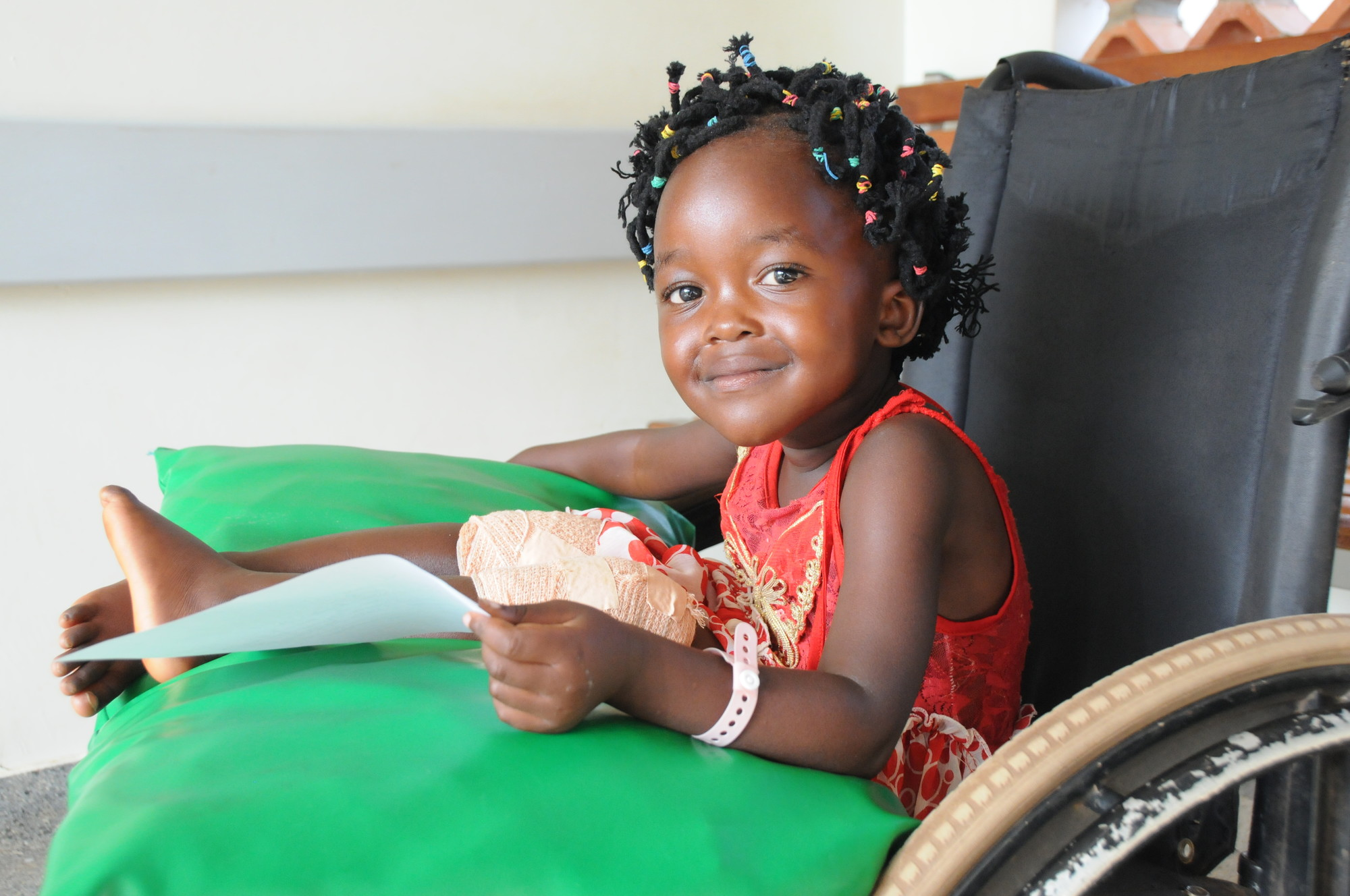 A happy Benita is waiting, sitting in a wheelchair, for her call to have another x-ray taken before being treated for her bowlegs.