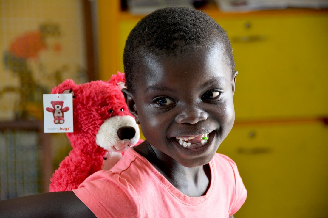 A girl smiles as she holds a teddy bear.