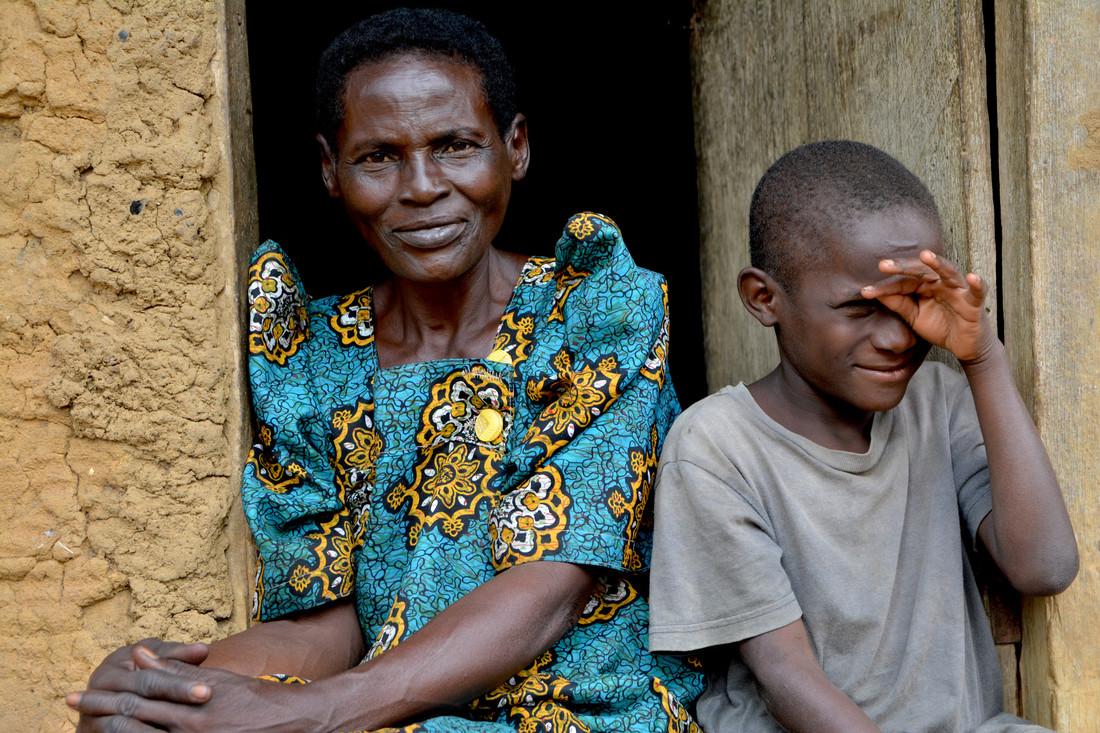 Mathias sitting with his grandmother in thier doorway.JPG