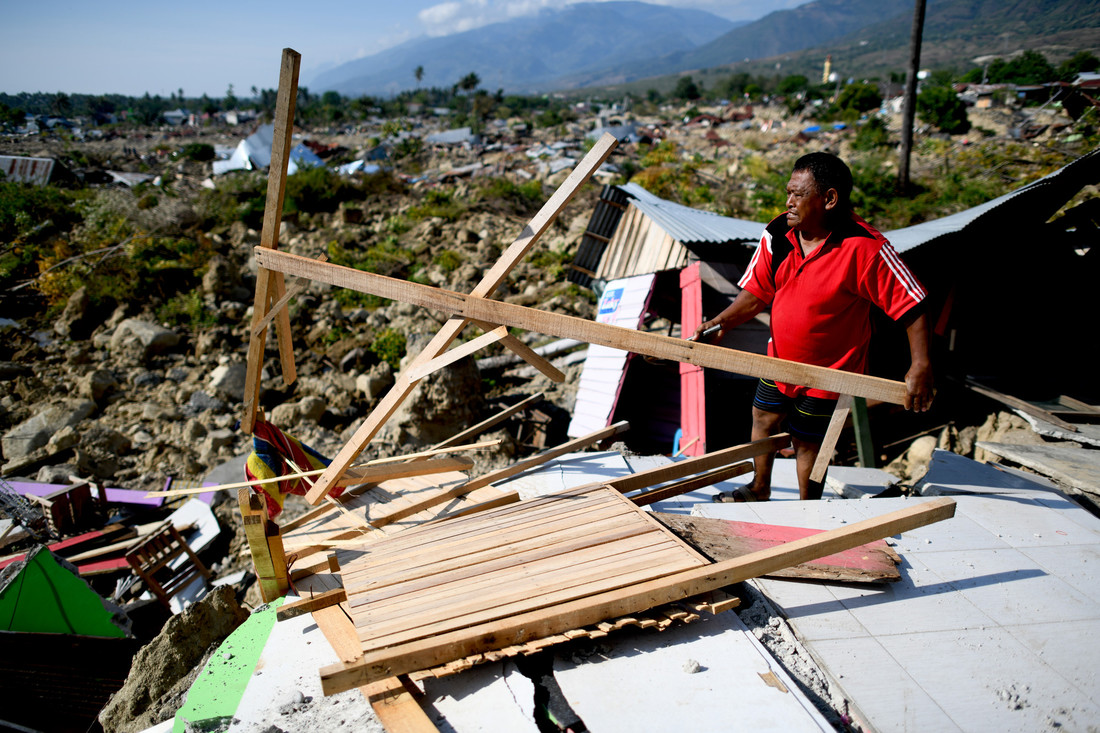 A survivor salvages useable items from the debris of a destroyed house in Palu