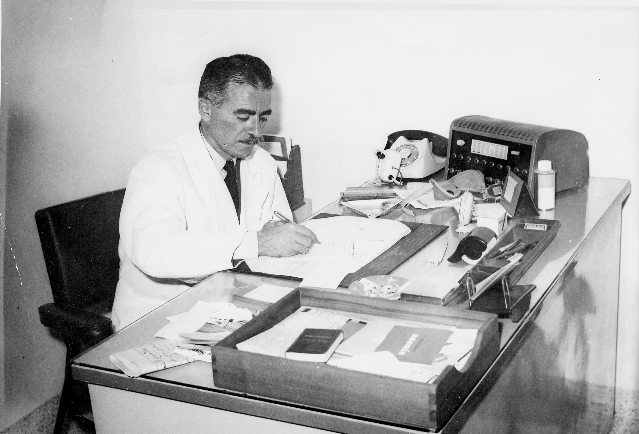 Dr. Sami Khoury in his clinic at Palestine Hospital in 1960 Amman Jordan writting prescription after seeing a patient