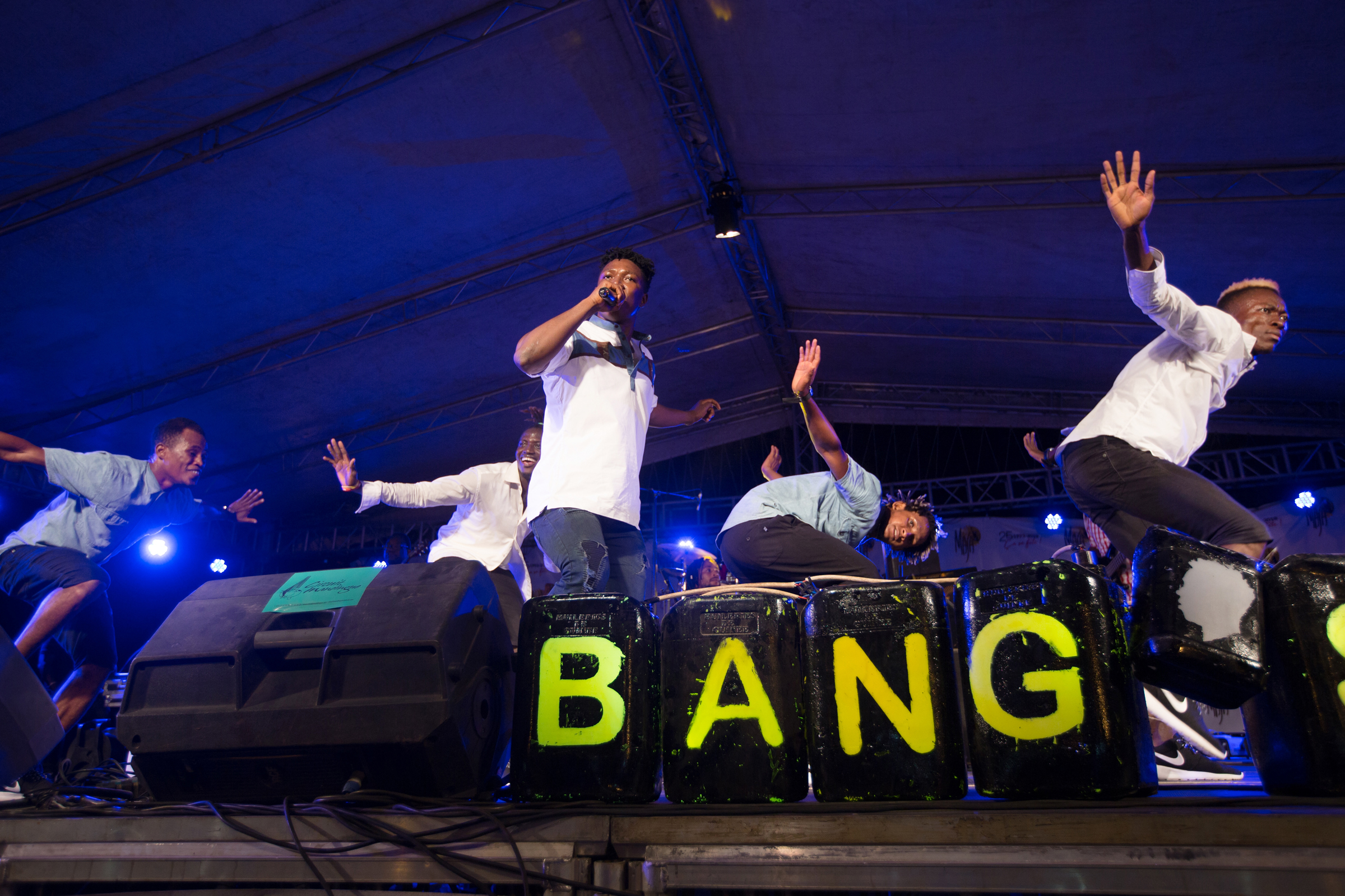 Soul Bangs, from Guinee Conakry led by singer Souleymane Bangoura, performing at the 2018 MASA festival. Old car tires were strewn across the stage and gas containers painted black with flourescent yellow spelling out the bands name. Behind Souleymane, four male dancers zig-zagged loosely choreographed routines, while the musicians stayed in the shadows laying down keyboard laden afro-soul grooves. Judging by the number of faans that breached the barriers and mobbed the performers backstage their upbeat and unpretentious personality is making waves beyond Guinee.