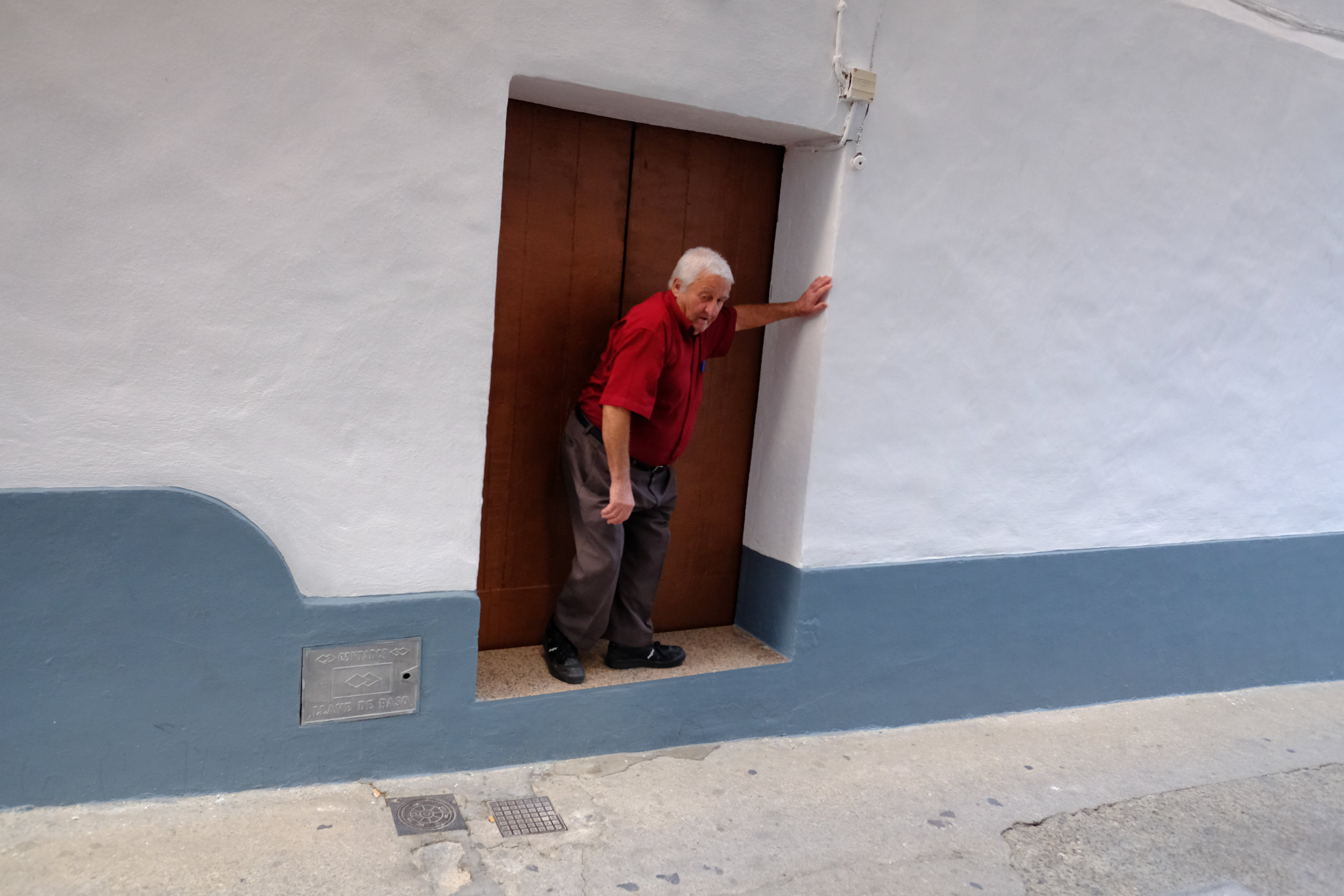 A man moving out of the narrow street to let a car pass by, Arcos de la Fronterra, Andalucia.