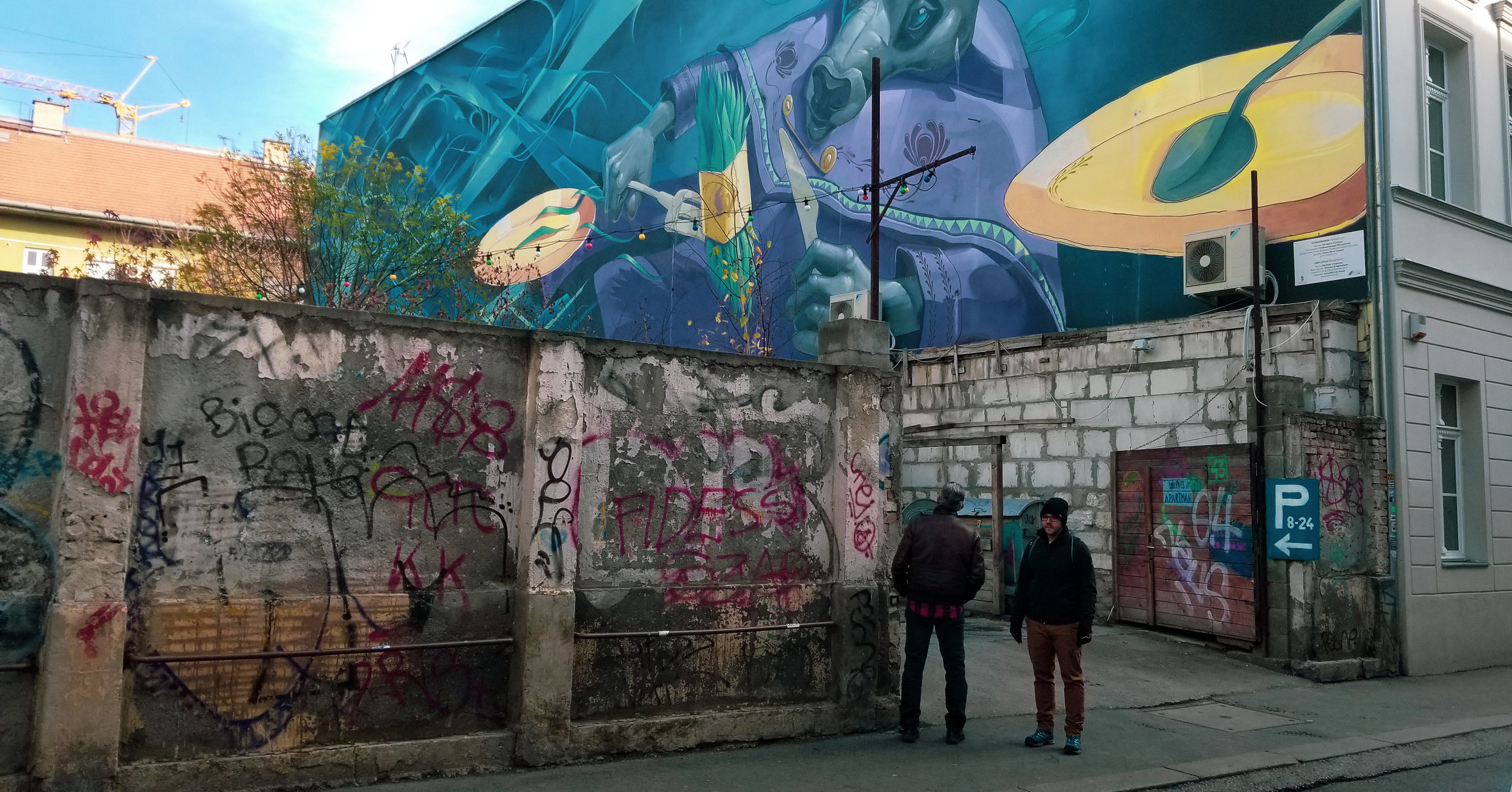This mural overlooks the garden at Mika Tivadar, a bar in Budapest's Jewish District, and represents Hungary's tradition of food and drink. Artist: Mika Tivadar ; Kazinczy u. 47