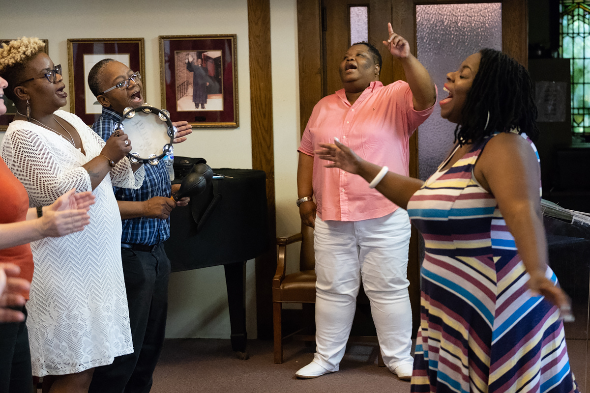 Rev. Shanea Leonard, the pastor of Judah Fellowship Christian Church, sings along with the congregation during worship. Anita Levels directs the worshipers in song.