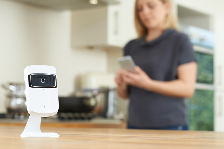 Woman Controlling Smart Security Camera Using App On Mobile Phone