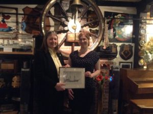 Myself and Crows Nest Officer's Club Chair, Margaret Morris, pose with a photograph of the  Thetis,  in front of the ship's wheel hanging in the Club.
