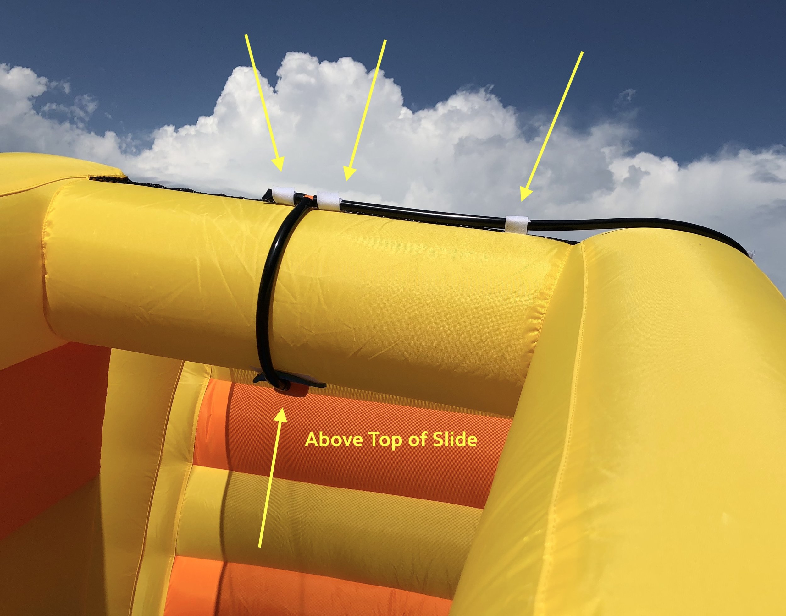 8d. Continue attaching hose around the front of the right slide.  Attach the sprinkler above the top of the right slide using Velcro.  8e. Attach garden hose and gently turn on water (1/2 turn should work).  EXCESS WATER PRESSURE CAN DAMAGE HOSES AND CONNECTORS.