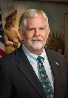 Robert Hutchinson - Hutch has also served three terms on the Alachua County Commission where he has chaired the Criminal Justice, Mental Health, Substance Abuse grant committee, and pushed the effort to have all county employees receive Mental Health First Aid training. He also serves on the boards of NAMI, the Community Foundation, the Wagmore Foundation.Hutch is the chief gravedigger at Prairie Creek Conservation Cemetery. He co-founded the intentional community of Flamingo Hammock where he fosters dogs and plays music with the Weeds of Eden.