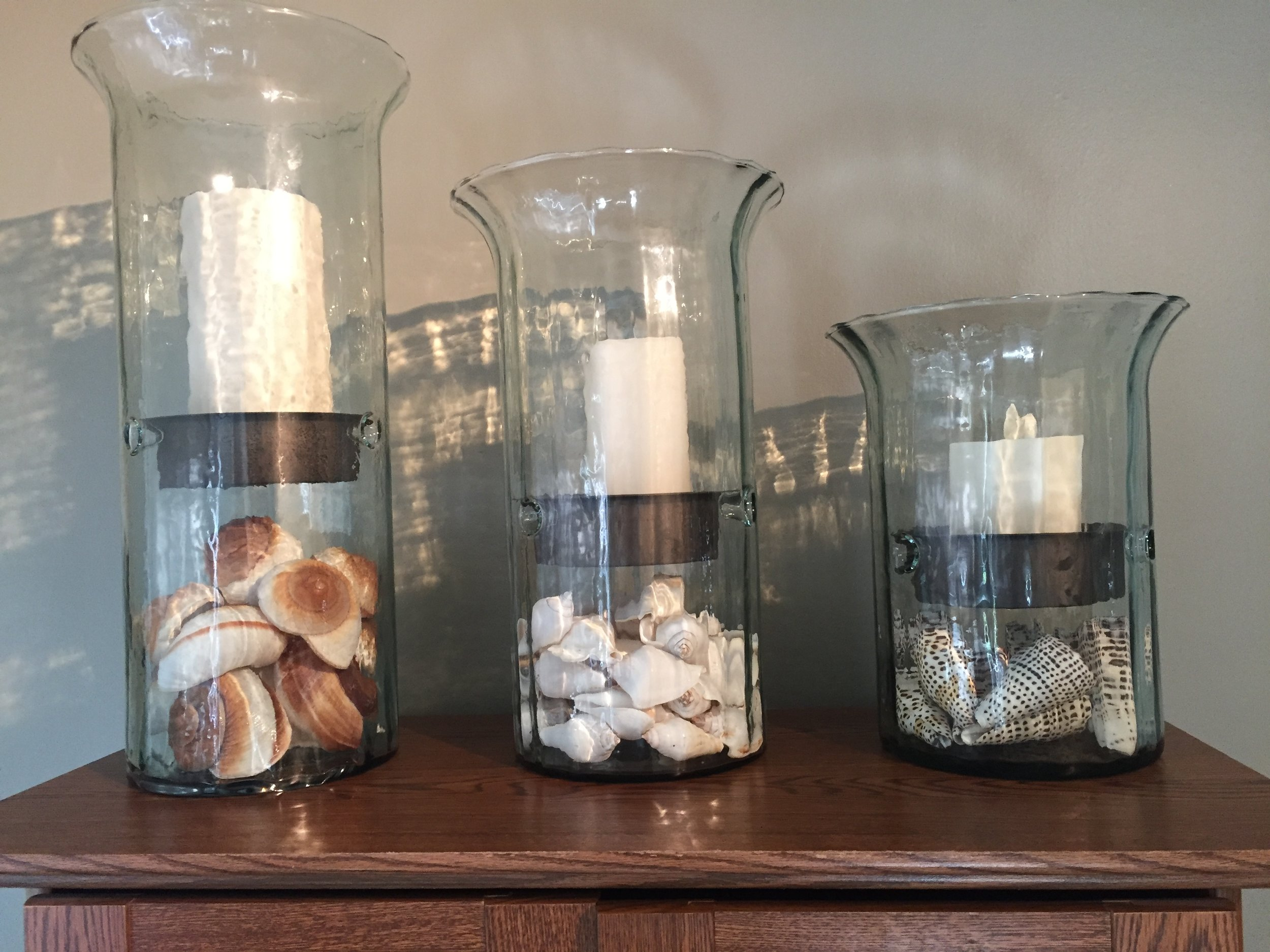 Hurricanes and Lanterns - Hurricanes and Lanterns are very versatile decor pieces. Both come in a variety of styles and sizes, and are easily changed by using different fillers and candles. They are a great basic decor piece with so many affordable choices. The Hurricanes pictured have different types of seashells as fillers for Summer.