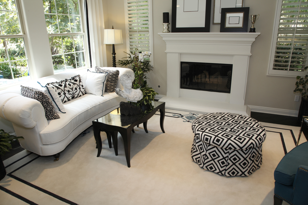 Beautiful White Roll Arm Sofa, dark wood coffee table and ottoman and pillows in black and white color palette with patterns.