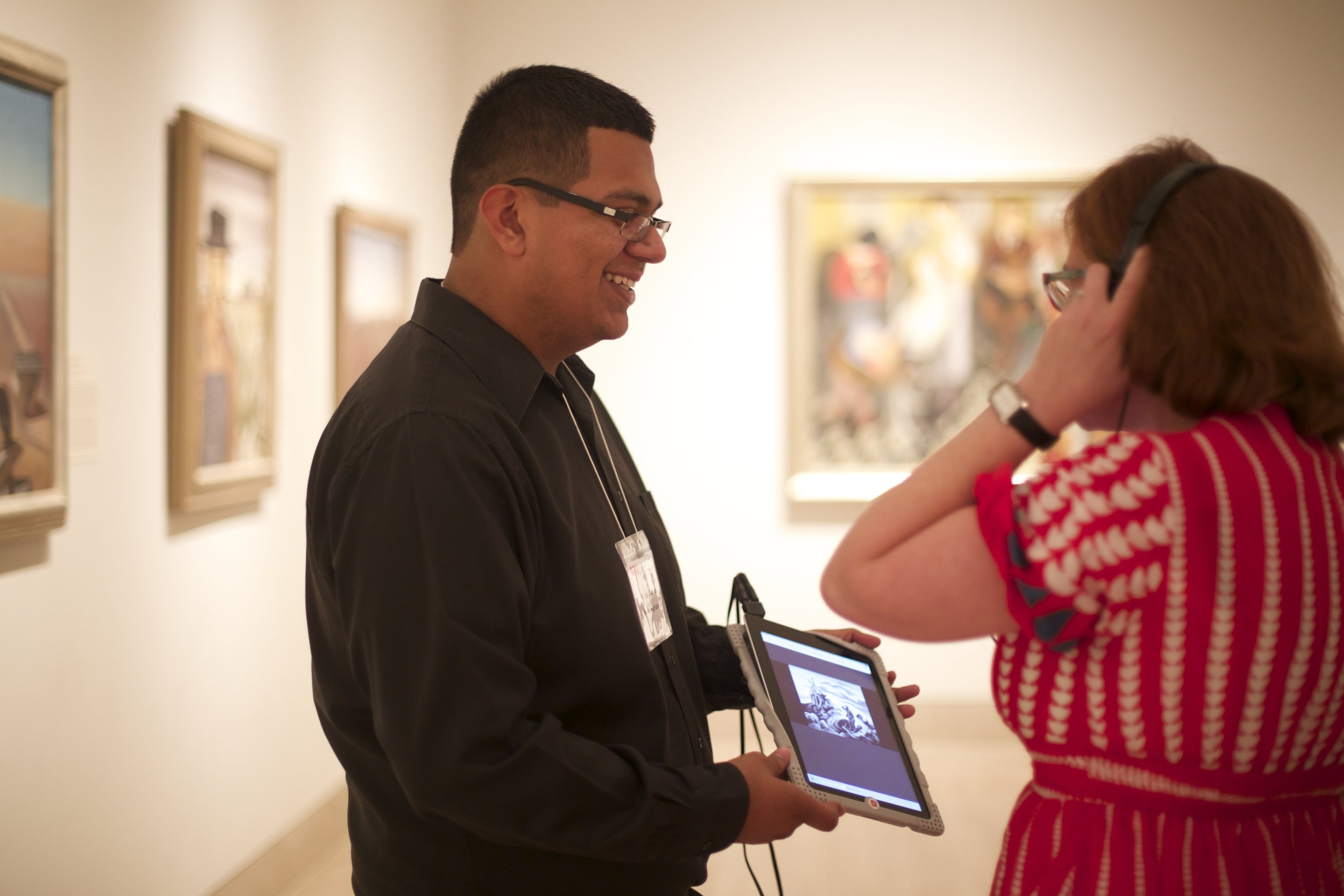 Miguel Mendez interacting with visitor at opening of MAP's Translating Culture 2 at Dallas Museum of Art. Photograph by Janeil Engelstad / Make Art with Purpose.