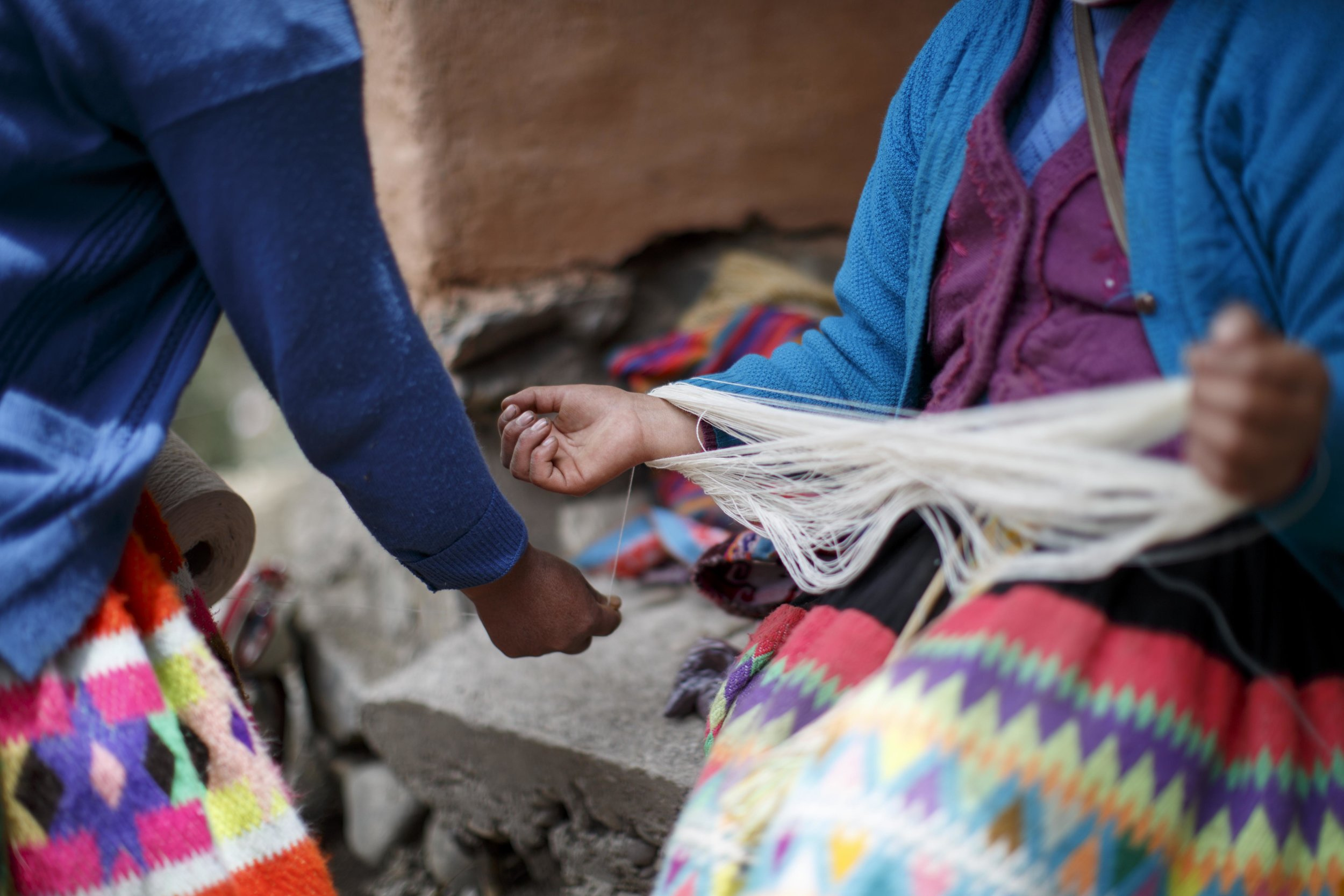 Artisans collecting the threads in a triangular pattern to stretch them across the backstrap loom.