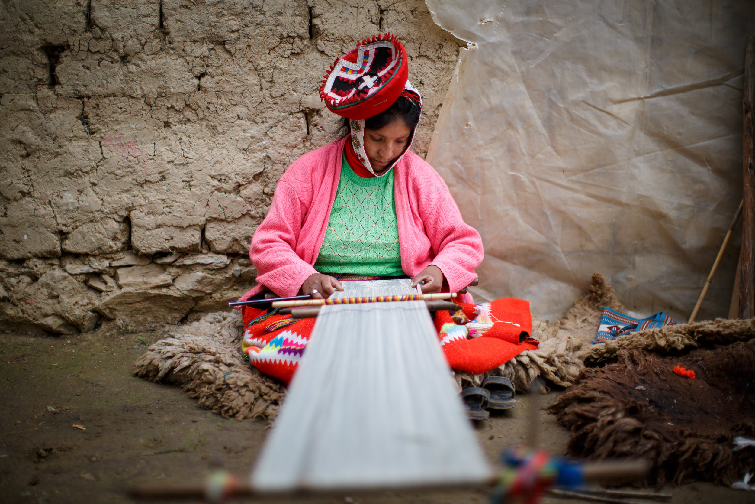 An artisan weaves threads into cloth on the backstrap loom.