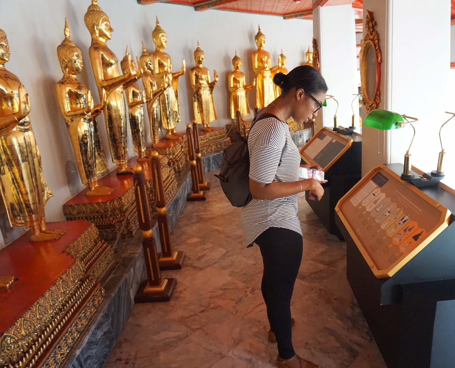 Reading the history about the temple surrounded by smaller Buddha images
