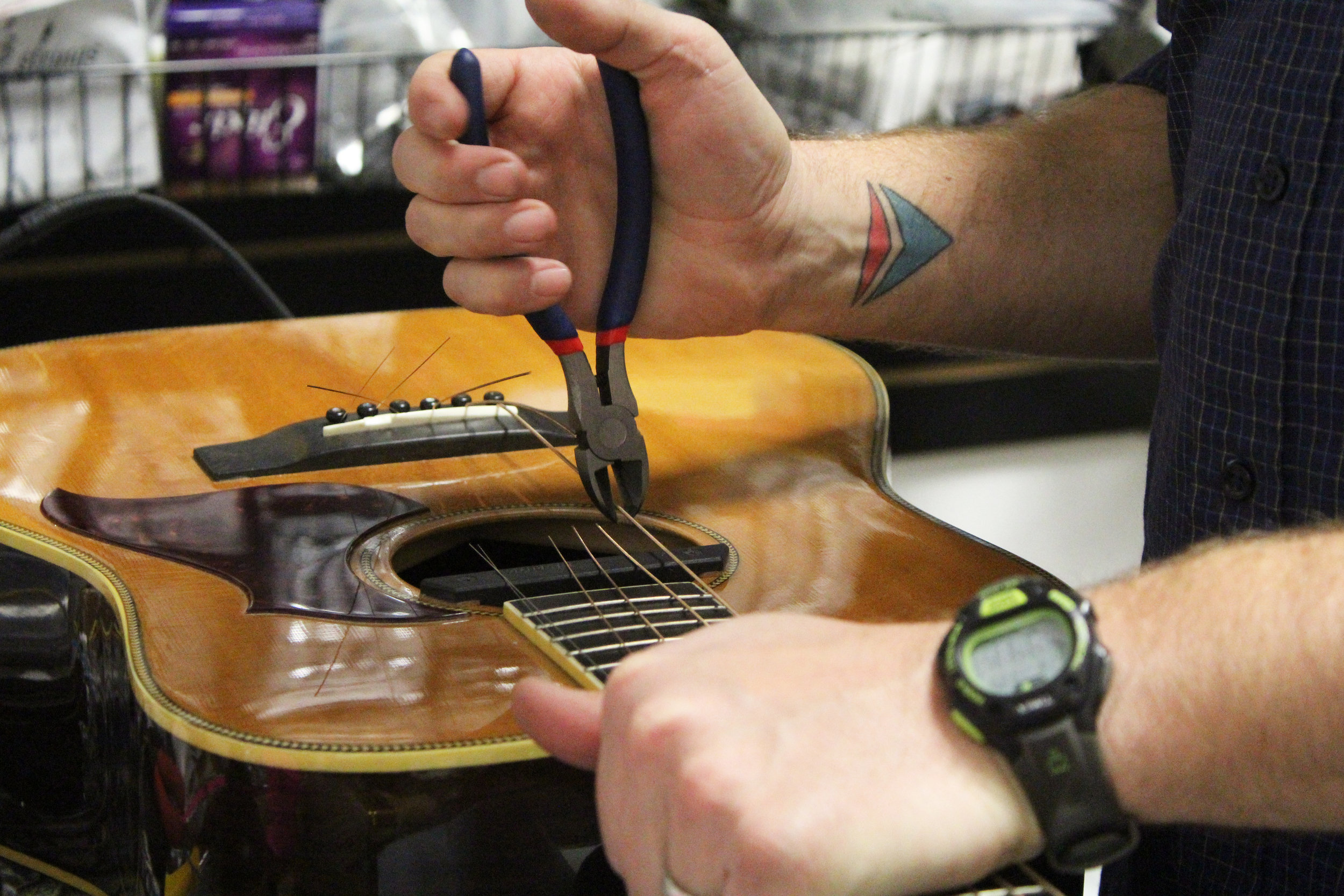 Brent Moore uses a wire cutter to cut loose strings, Friday, Jan. 19, 2018, at CoMo Guitar Works. CoMo Guitar Works is located in the used instrument store, Music Go Round, off Broadway in Columbia, Mo.