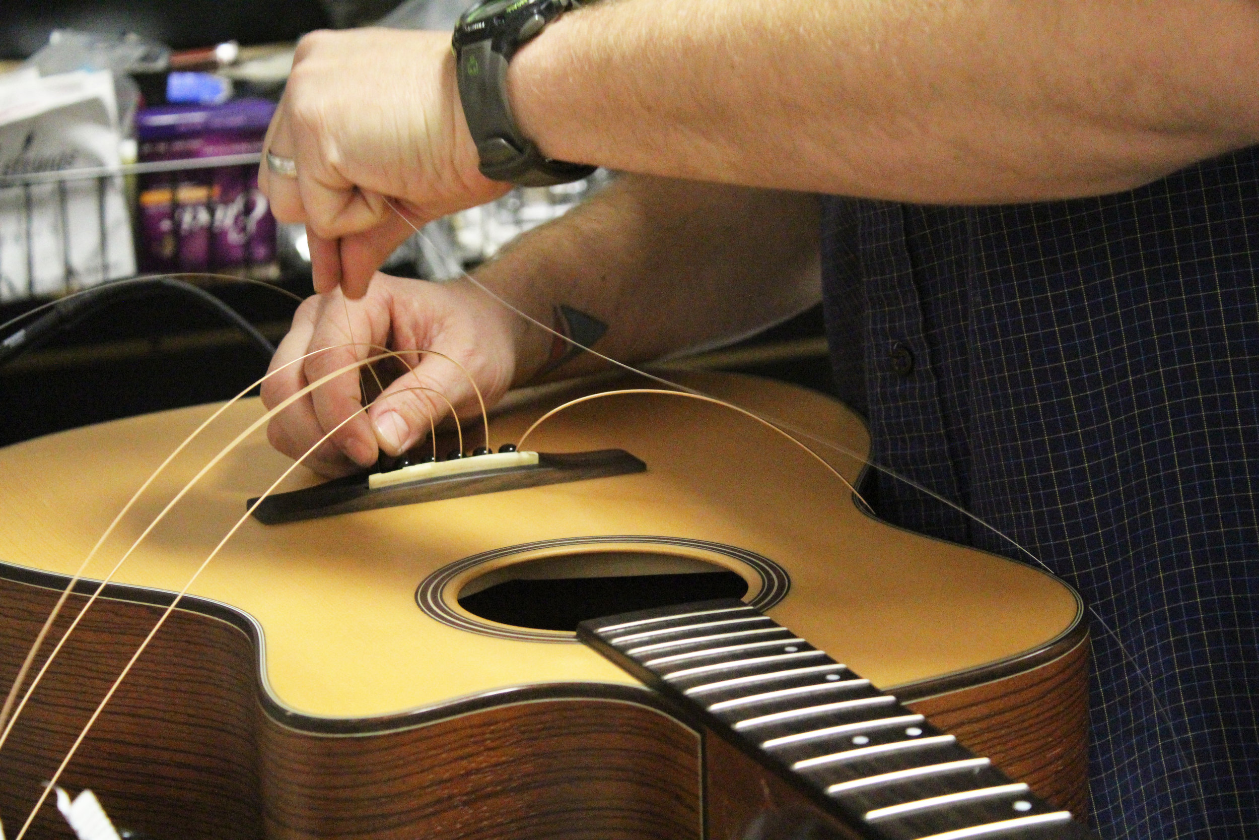 Brent Moore replaces guitar strings on Friday, Jan. 19, 2018, at CoMo Guitar Works in Columbia, Mo. Moore put in a taller bridge on the guitar so the strings will have more room.