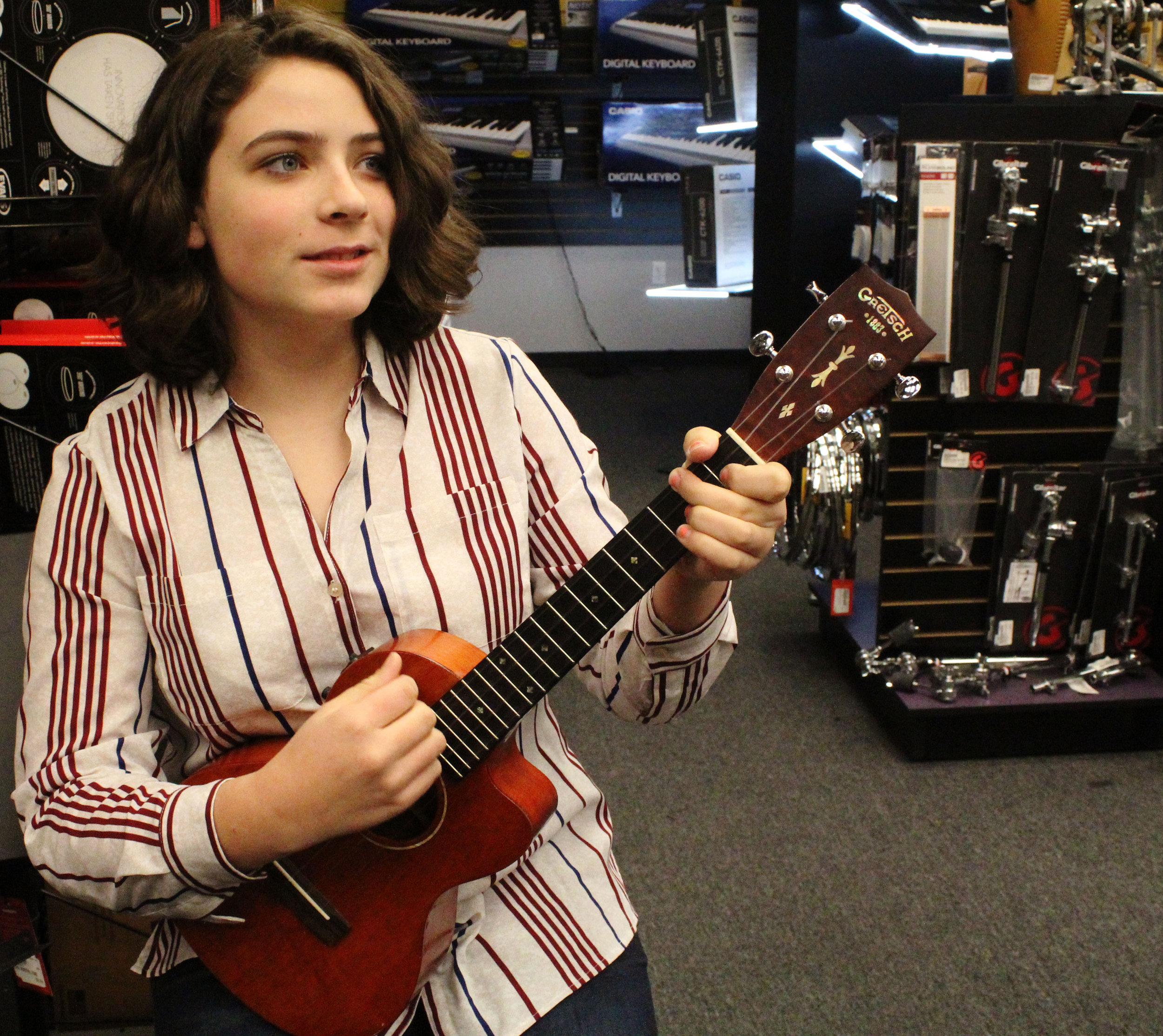 "Olivia Burney, a customer of CoMo Guitar Works, plays with her newly repaired ukulele on Friday, Jan. 19, 2018 at CoMo Guitar Works in Columbia, Mo. Burney says she trusts Brent's work and is happy that her ukulele plays well. ""He put in a new bridge for this and it sounds really awesome. I just think it's really, really, really cool,"" Burney said."