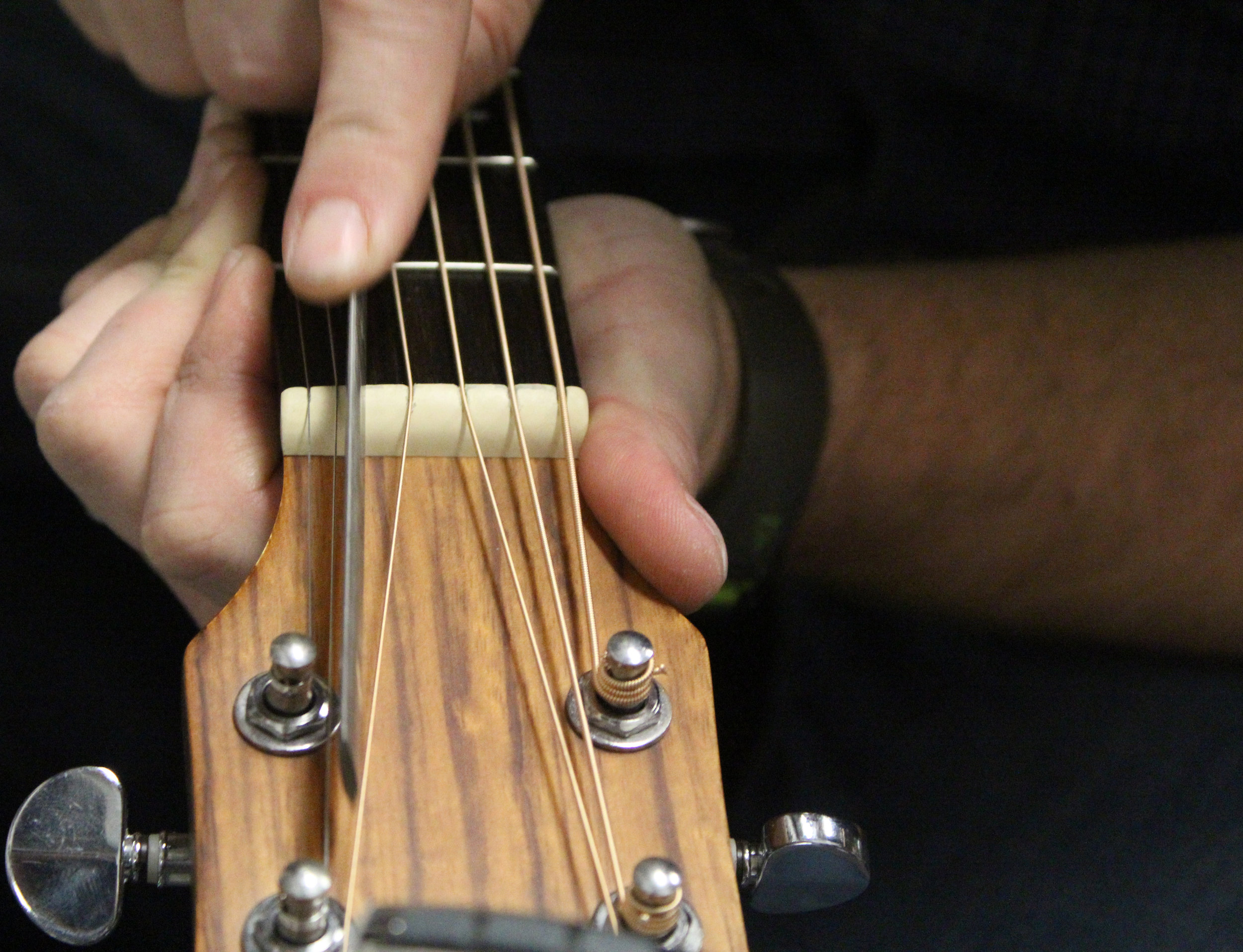 "Brent Moore files the guitar nut on Friday, Jan. 19, 2018, at CoMo Guitar Works in Columbia, Mo. ""We've come down here to ask him some questions about pickups and stuff,"" Olivia Burney said. ""He's been really, really helpful."""
