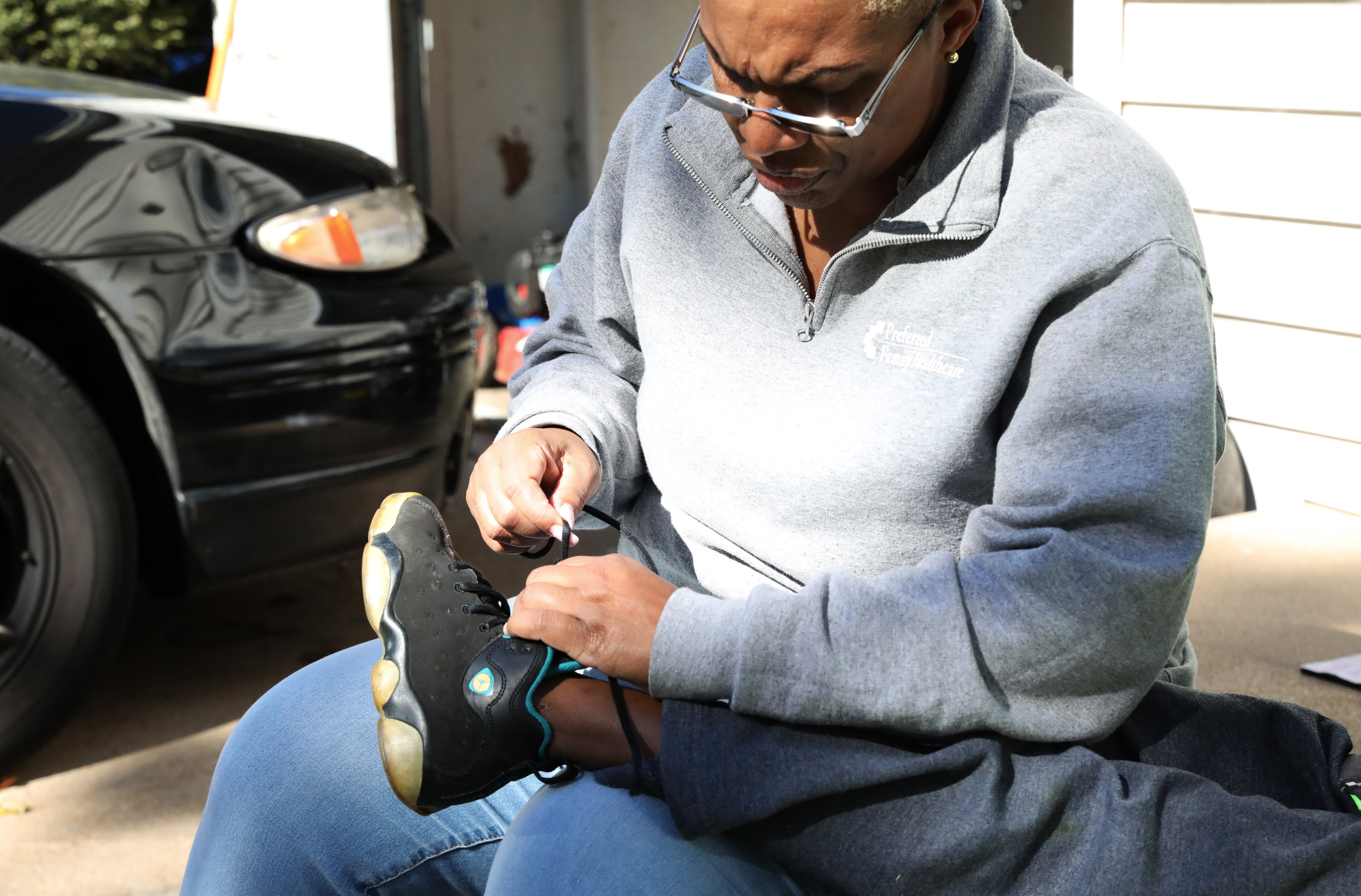 "Erica Jones sits on the stairs in front of her house and helps her grandson Ja'Keem Jones to tie his shoe on Sunday, Oct.28, 2018 in Florissant, Missouri. ""I'm the grandmother that always has our grandkids on matter what,"" Erica said. ""We're very close-knit family so we are always with one another."" (Photo by Yanran Huang)"
