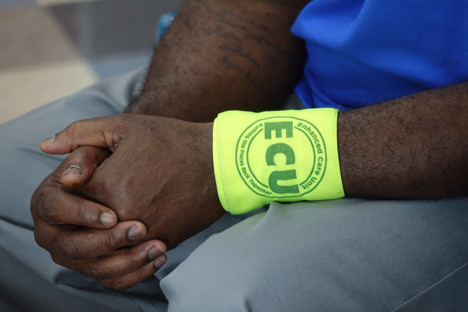 "Anthony Paine holds his hands with his Enhanced Care Unites band on his wrist at Jefferson City Correctional Center on Tuesday, April 3, 2018 in Jefferson City, Mo. As a daily living assistant, he assists elderly prisoners and said he thinks respect is an important part of the program. ""You know, we are all humans, and when you help them you have to give them their dignity,"" Paine said.(Photo by Jiayi Shi)"