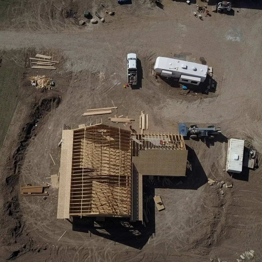 videoblocks-aerial-rural-farm-home-under-construction-climbing-overhead-4k-982-aerial-rural-farm-house-carpenters-work-to-build-new-construction-wood-lumber-frame-seasonal-rural-farm-community-homes-barns-and-buildings_s-gbjeuerl_thumbnail-.png